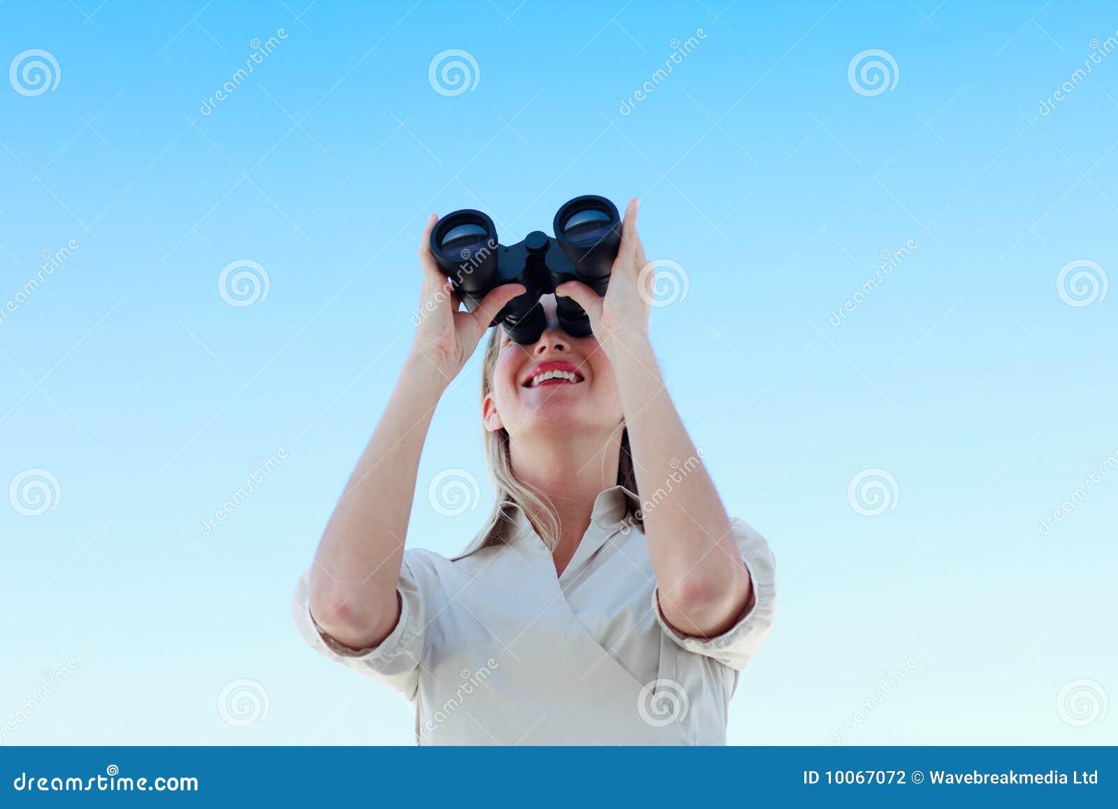 Mulher de negócios que olha através dos binóculos ao ar livre