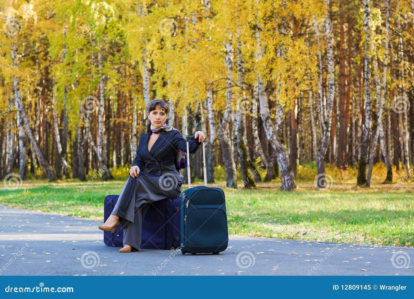 Mulher de negócios que senta-se em uma bagagem.