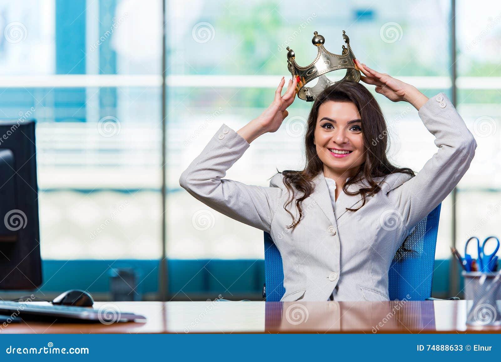 A mulher de negócios que senta-se na mesa de escritório