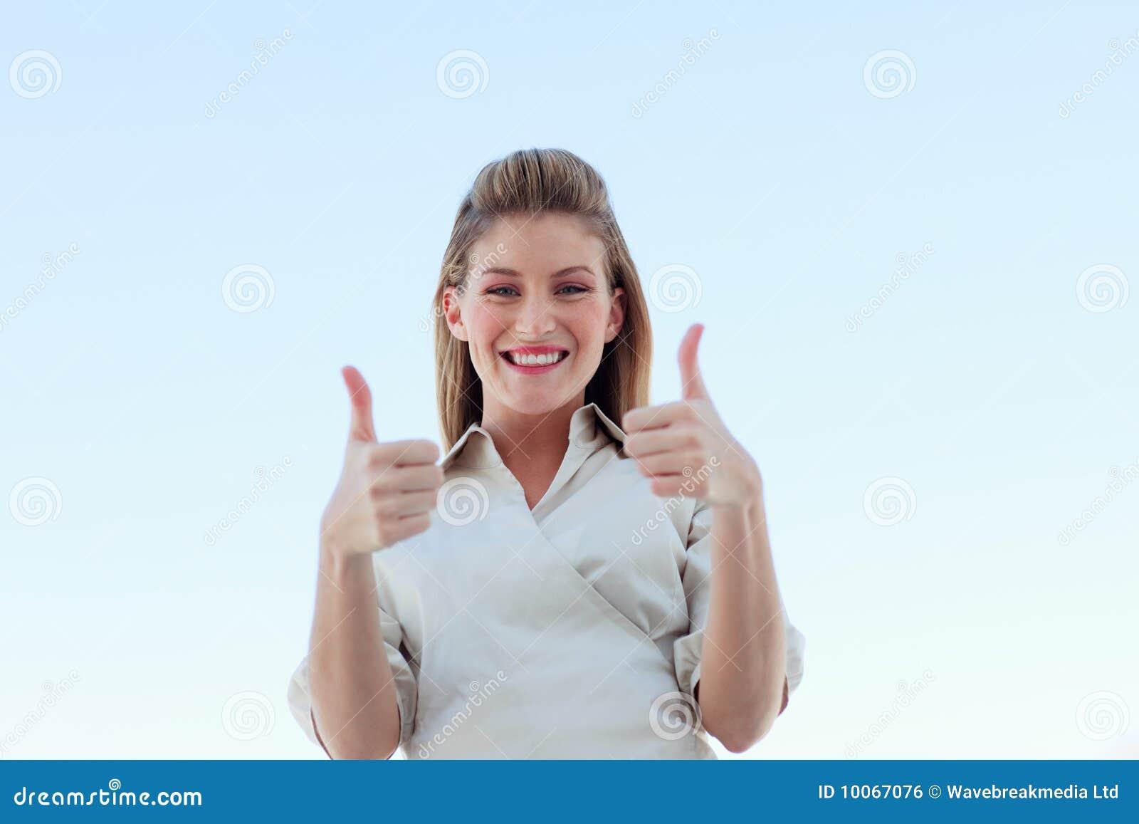 Mulher de negócios que sorri na câmera com polegares acima