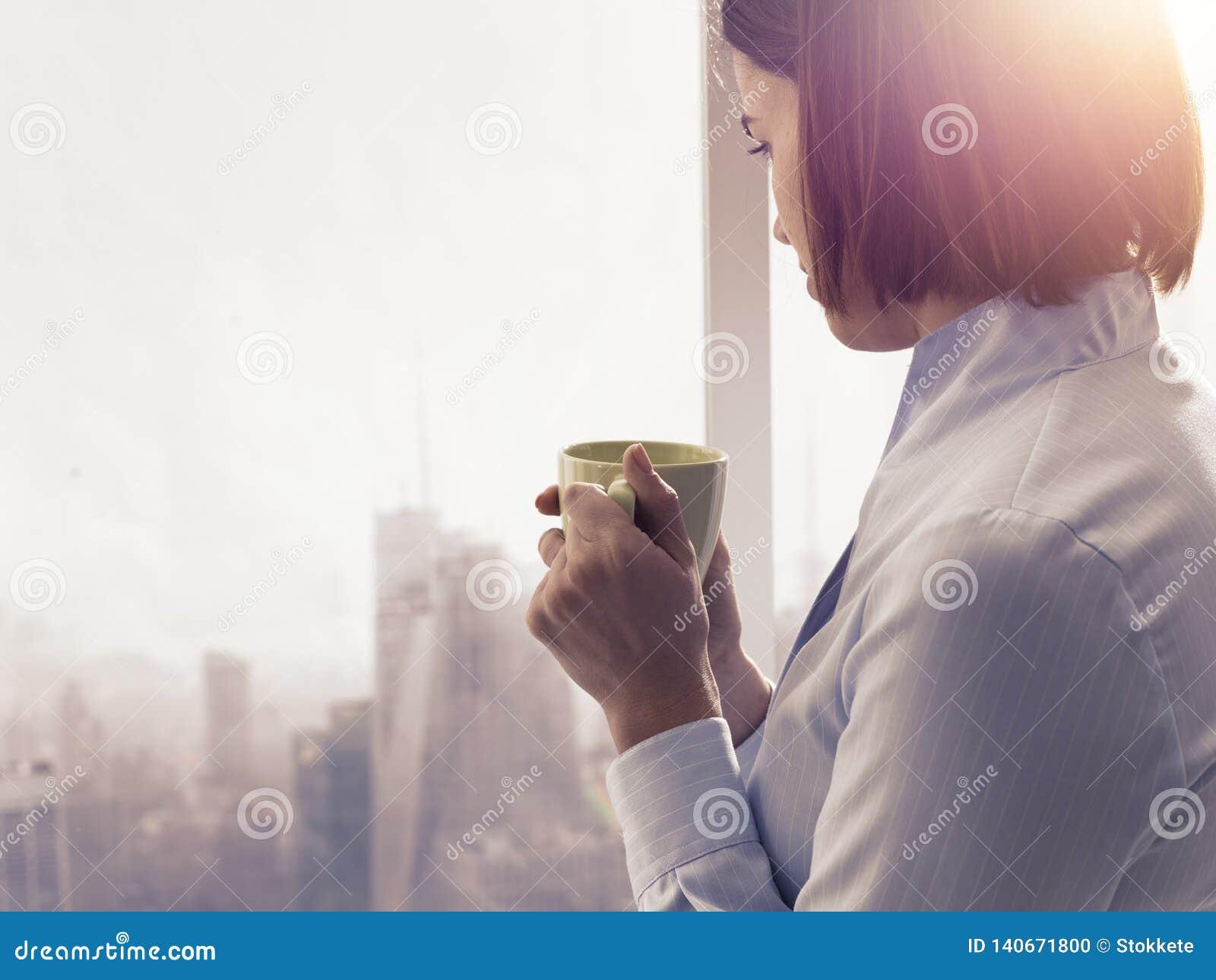 Mulher de negócios que tem uma ruptura de café de relaxamento