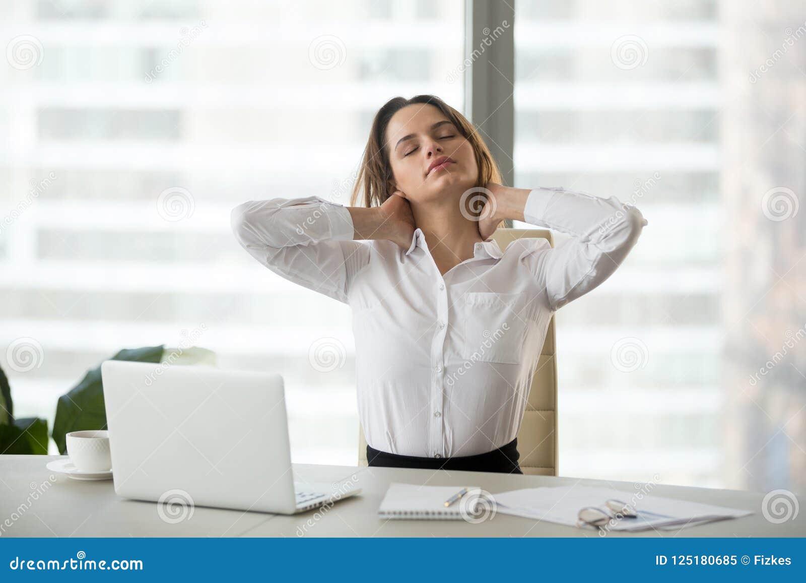Mulher de negócios que toma a ruptura de trabalho que faz a massagem dos exercícios do escritório