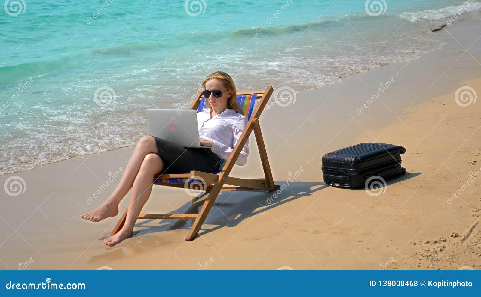 Mulher de negócios que trabalha em um portátil ao sentar-se em um vadio pelo mar em um Sandy Beach branco autônomo ou workaholism