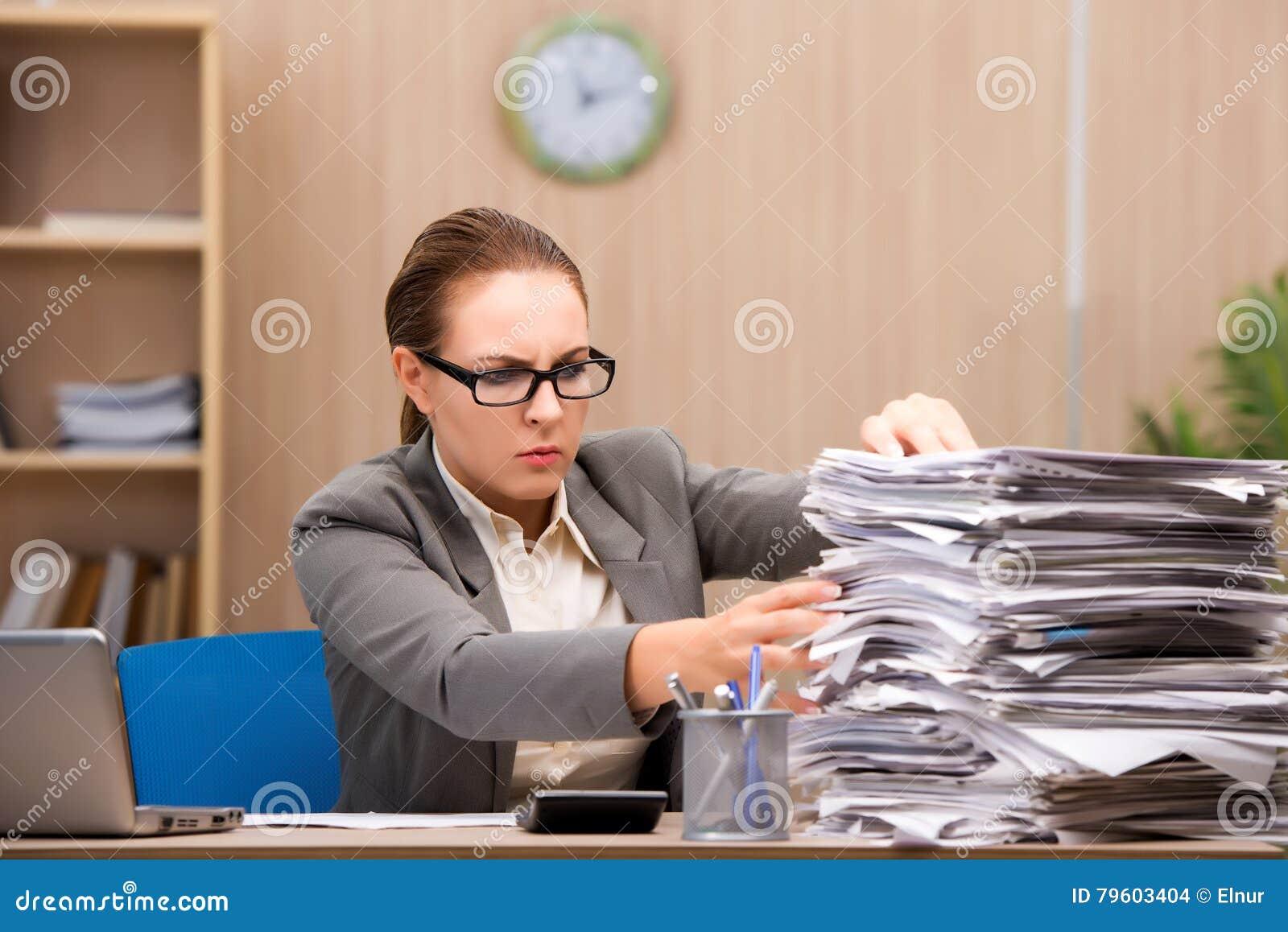 A mulher de negócios sob o esforço de demasiado trabalho no escritório