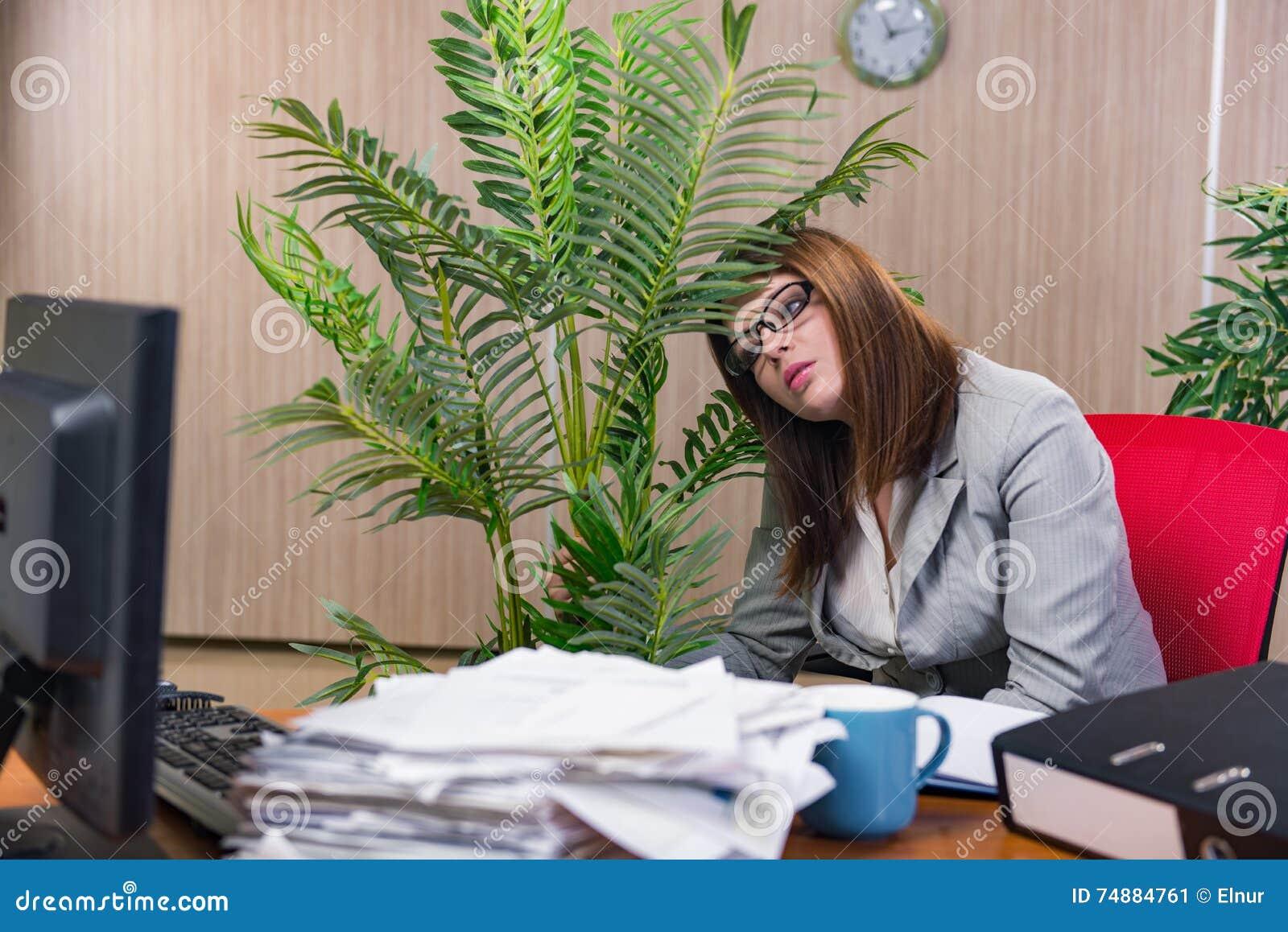 A mulher de negócios sob o esforço que trabalha no escritório