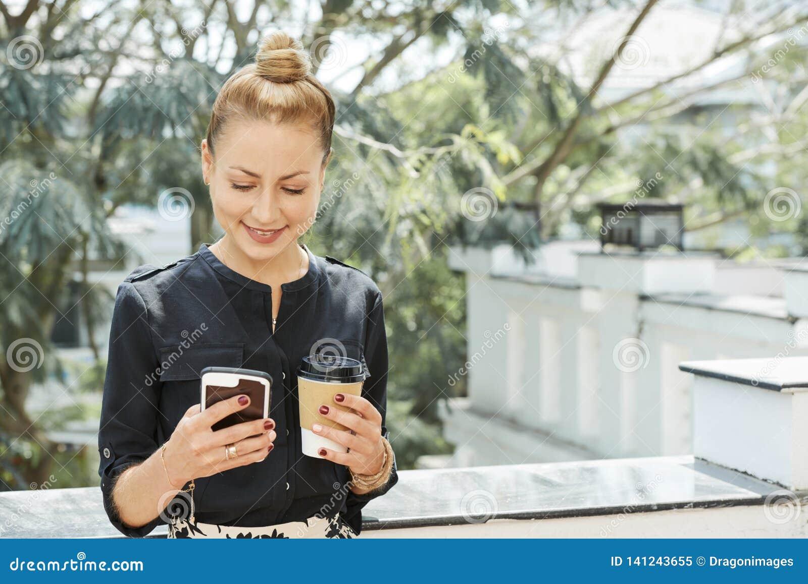 Mulher de negócios de sorriso com café e telefone