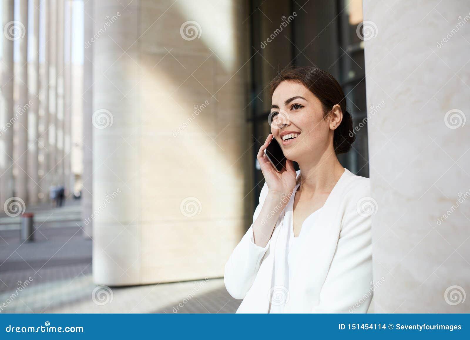 Mulher de negócios de sorriso Speaking pelo telefone