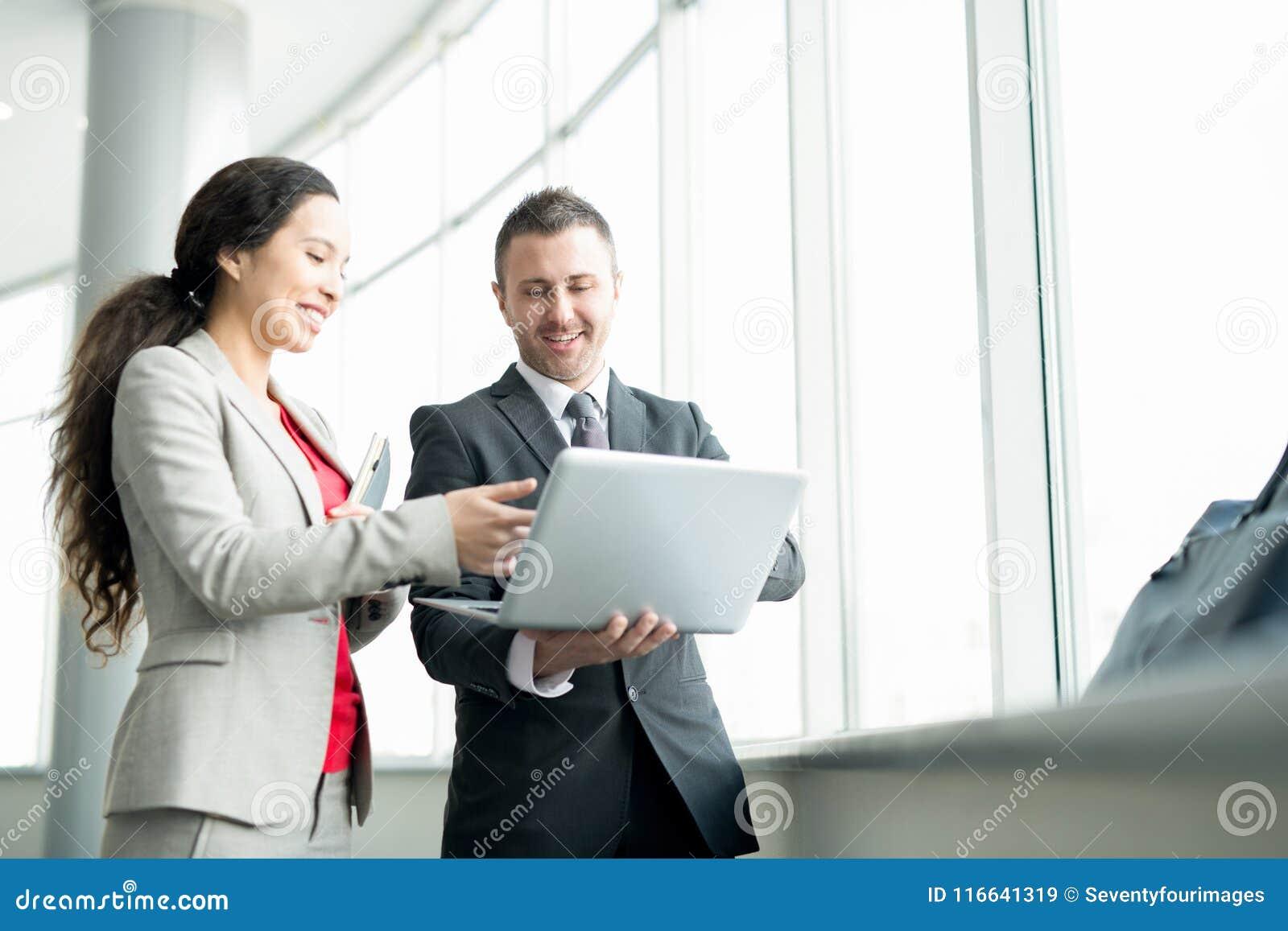 Mulher de negócios de sorriso Talking ao colega pela janela