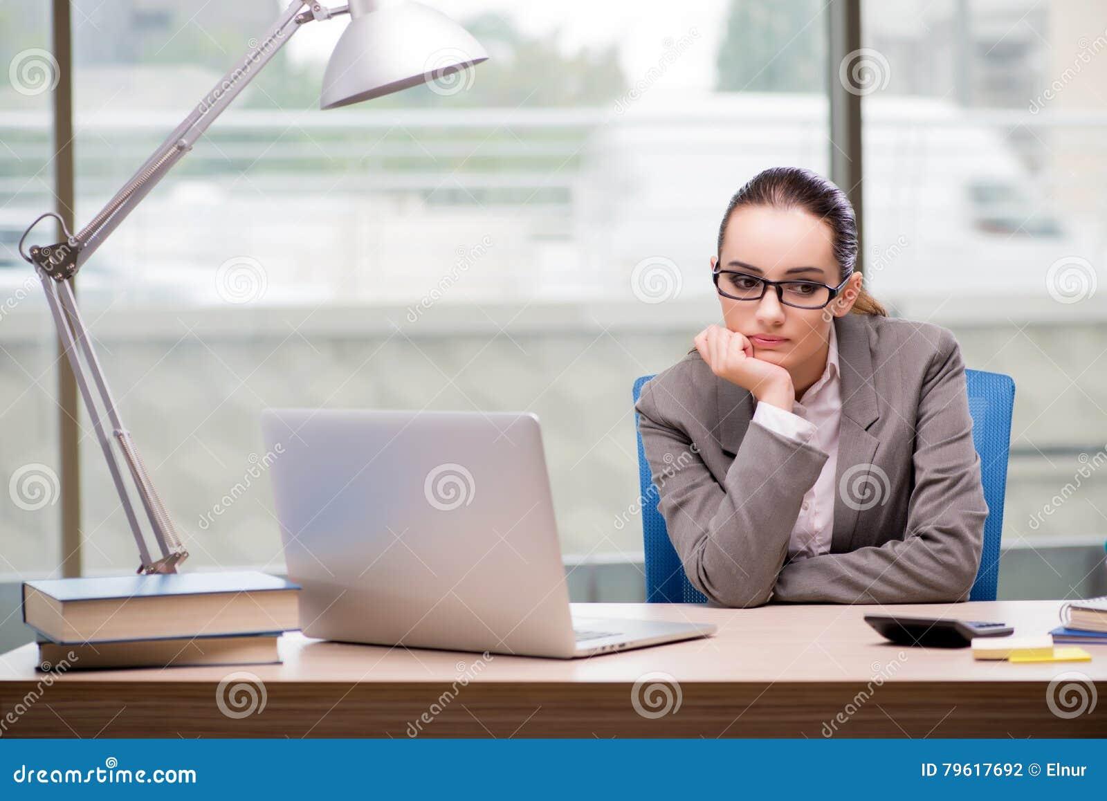 A mulher de negócios triste que trabalha em sua mesa
