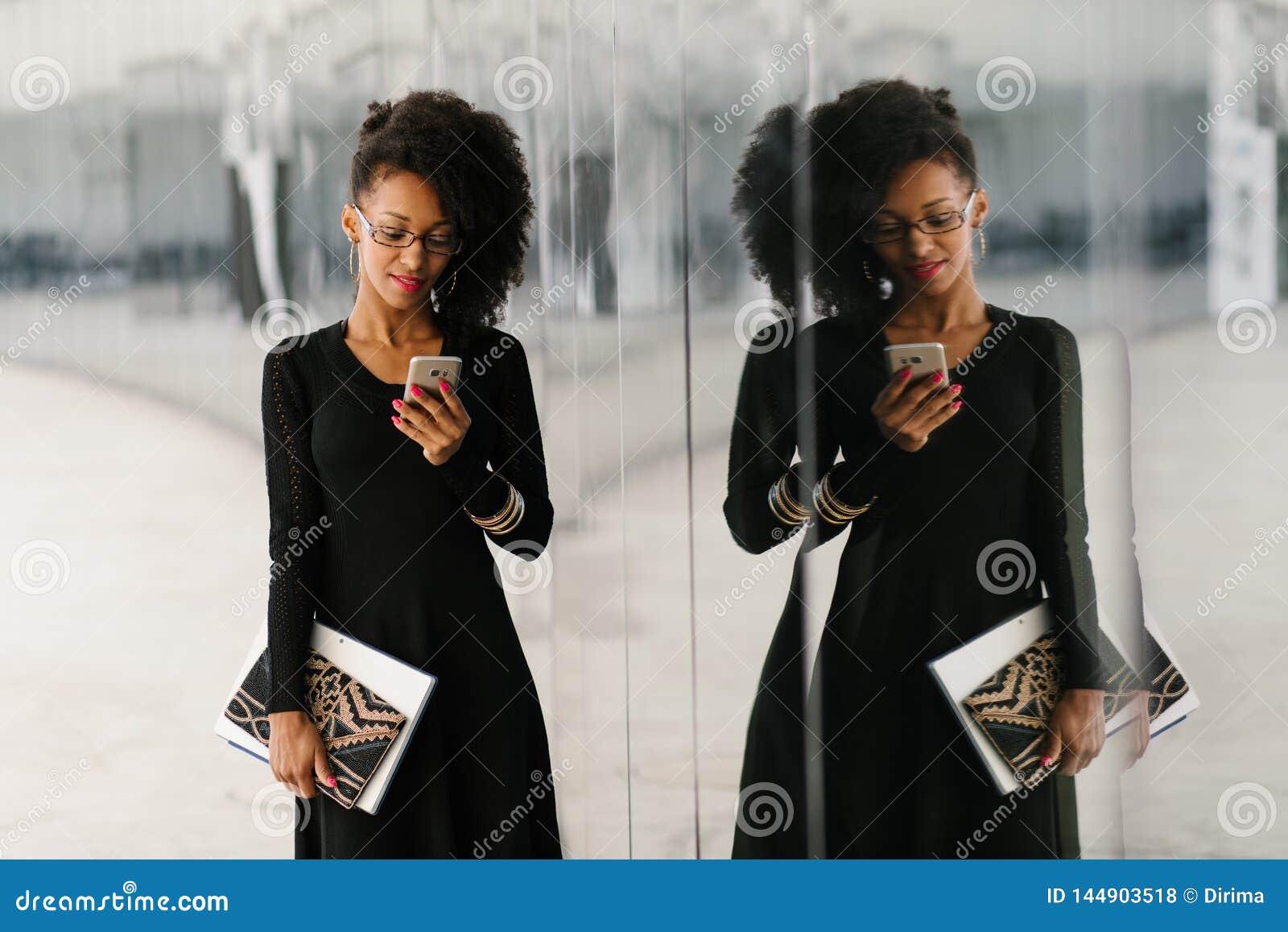 Mulher de neg?cios elegante nova que usa o telefone celular