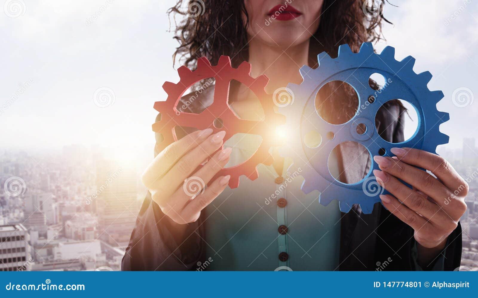 A mulher de neg?cios tenta conectar partes das engrenagens Conceito dos trabalhos de equipe, da parceria e da integra??o