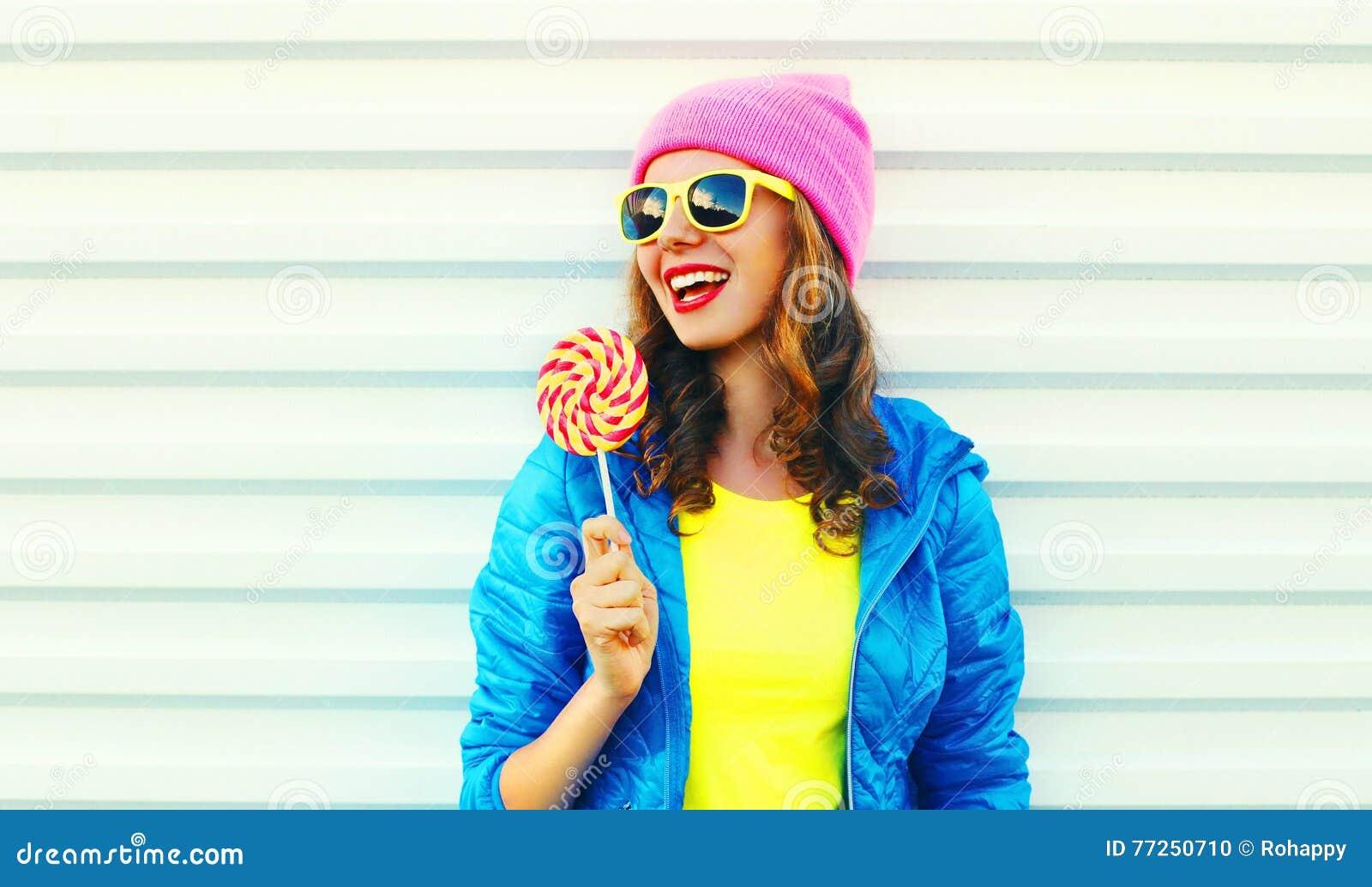Mulher de riso consideravelmente fresca da forma do retrato com o pirulito na roupa colorida sobre o fundo branco que veste um ch