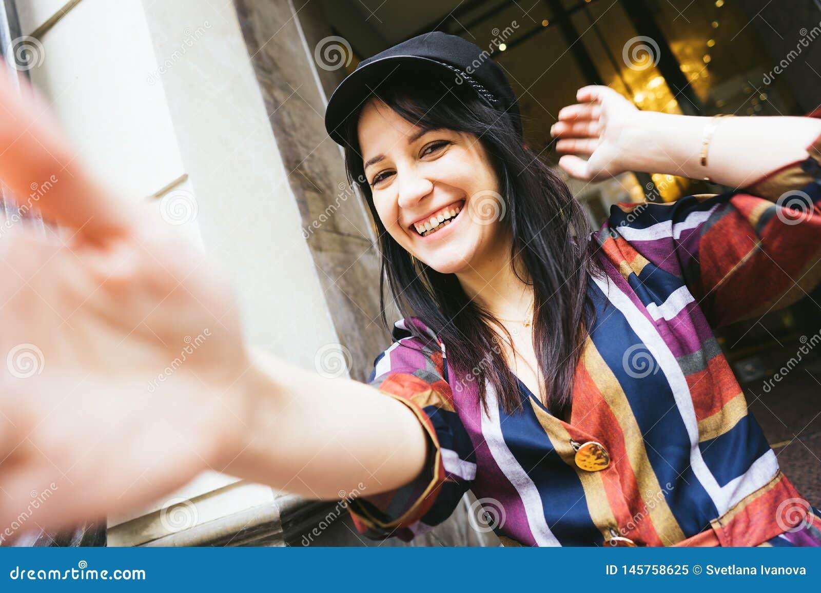 Mulher de riso feliz da raça misturada em um vestido listrado multi-colorido