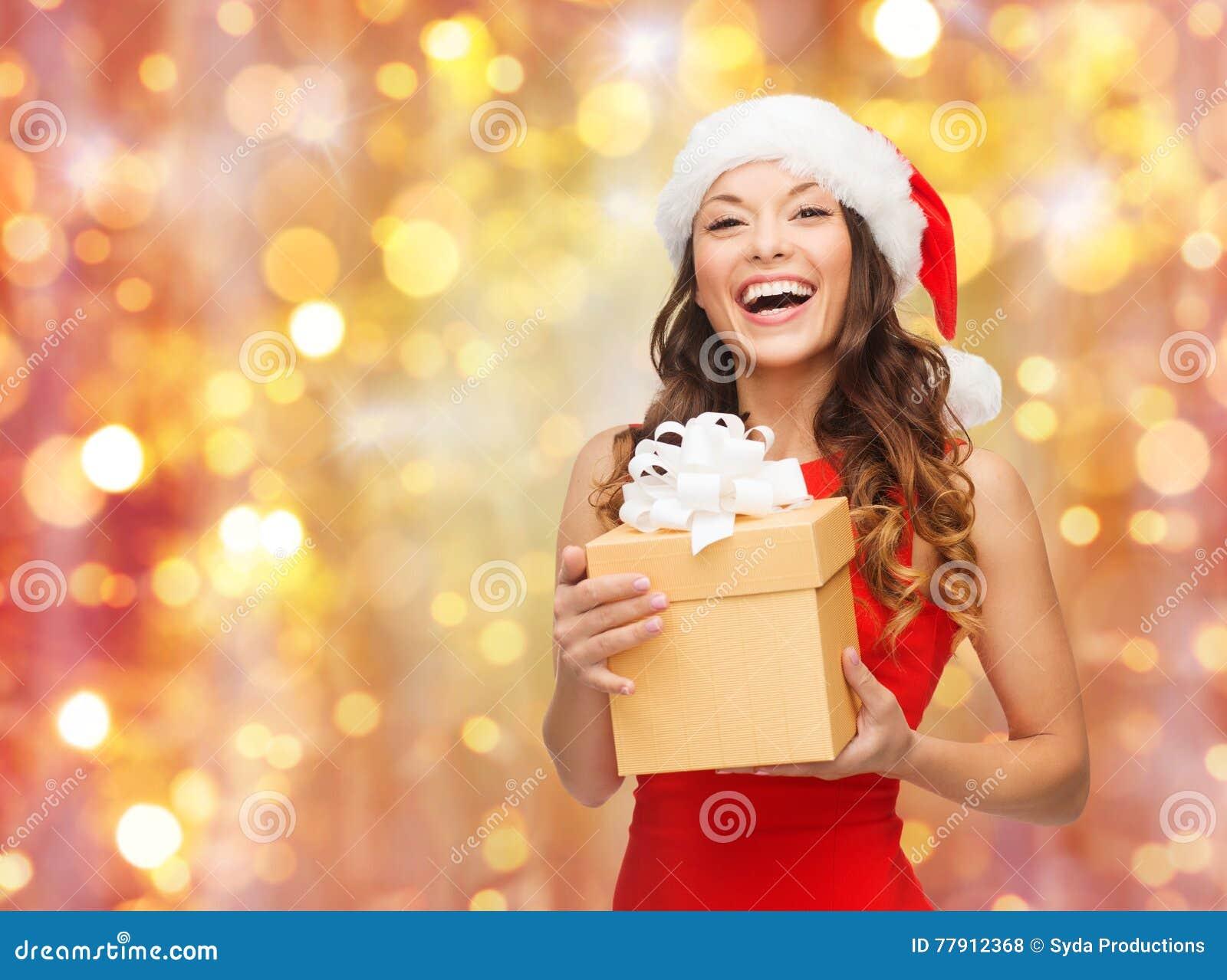 Mulher de riso no chapéu de Santa com presente do Natal