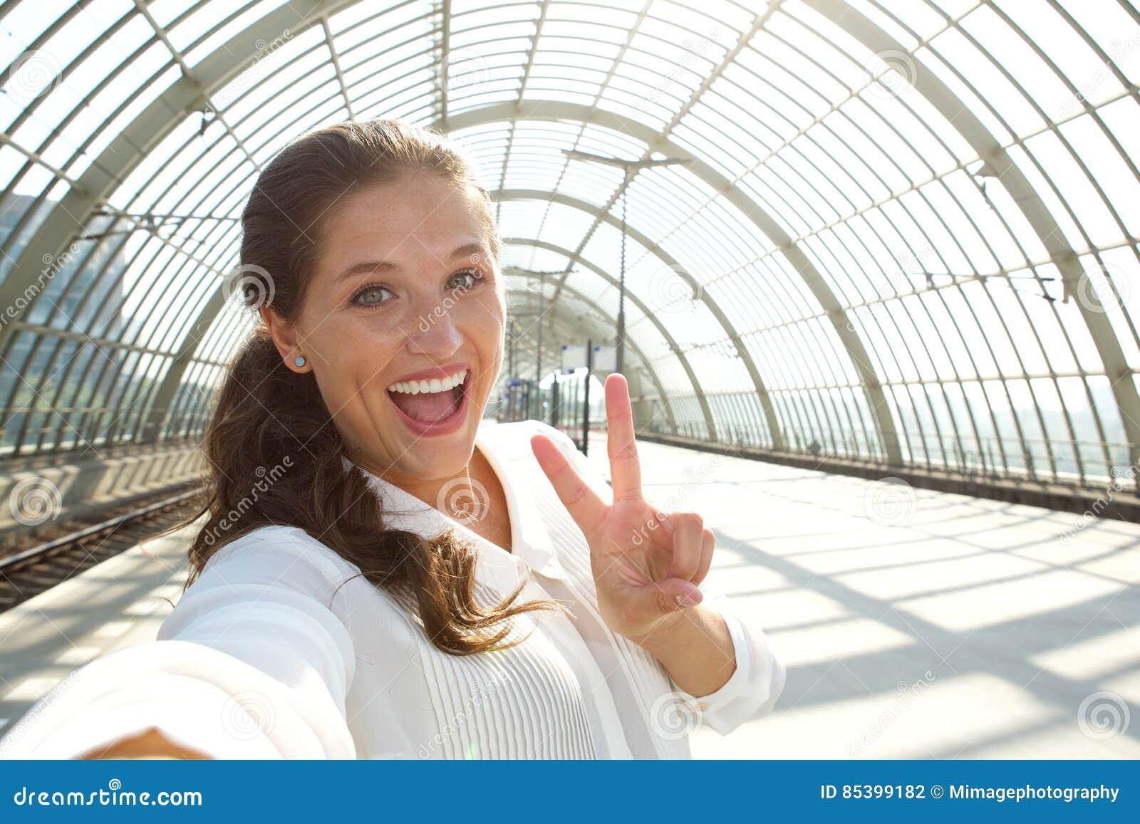 Mulher de riso nova que toma o selfie com sinal de paz