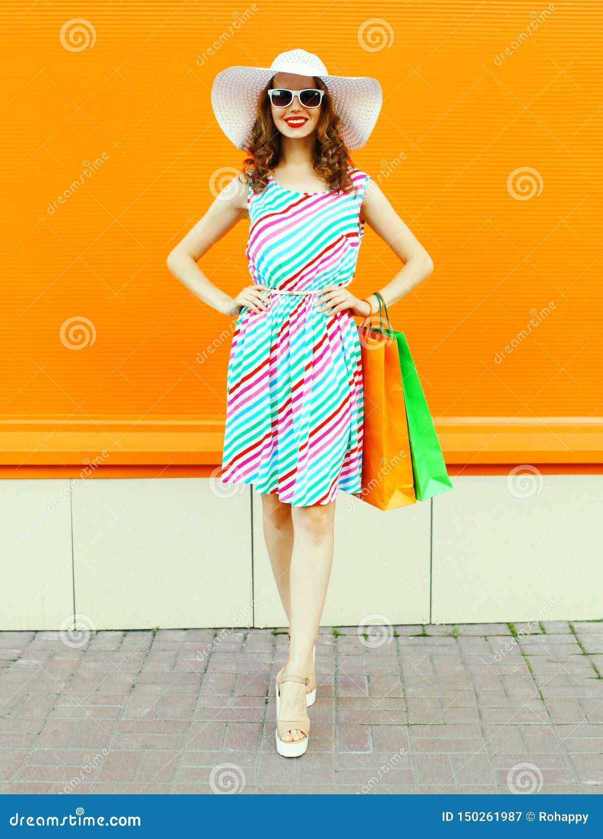 Mulher de sorriso à moda com os sacos de compras que vestem o vestido listrado colorido, chapéu de palha do verão que levanta na