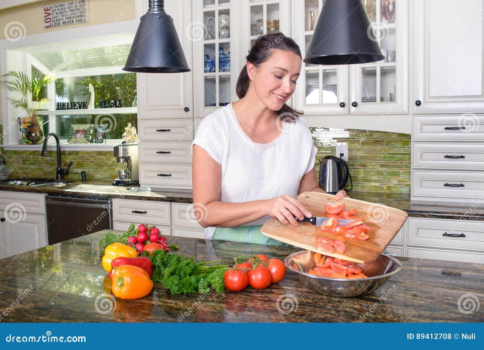 Mulher de sorriso atrativa que faz a salada em sua cozinha ensolarada