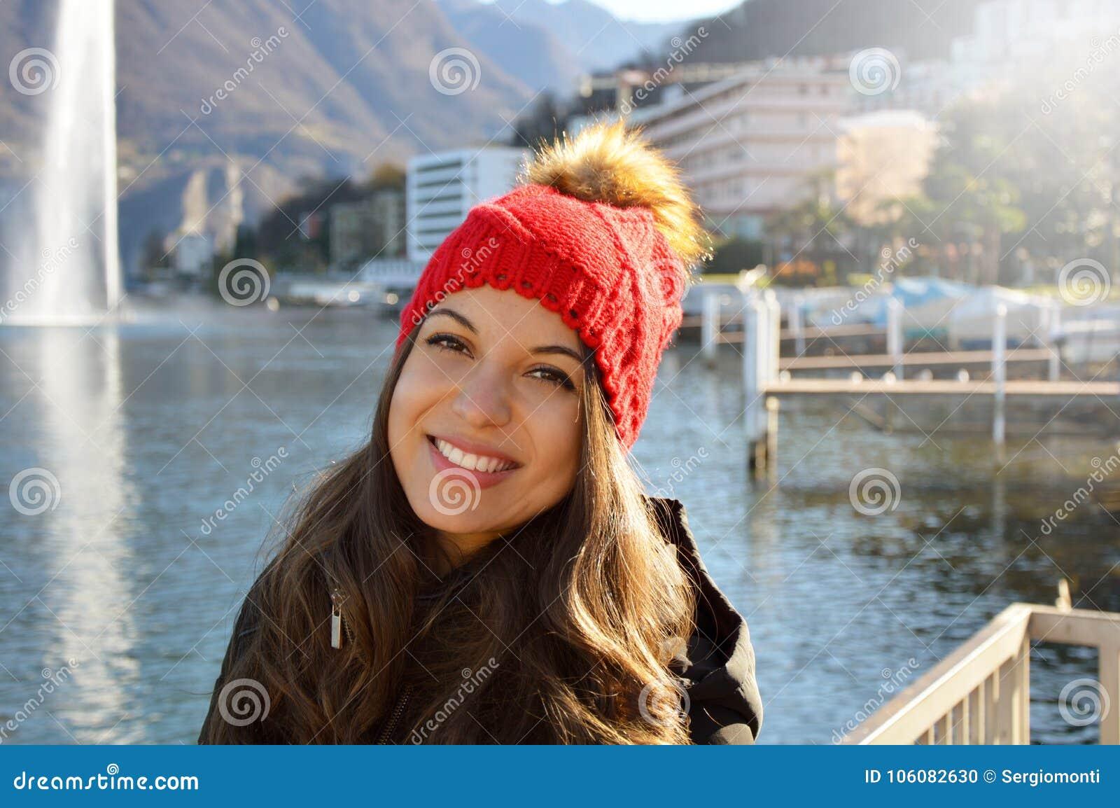 A mulher de sorriso bonita com dentes brancos e inverno veste-se fora com o lago suíço no fundo e na luz do sol clara do alargame