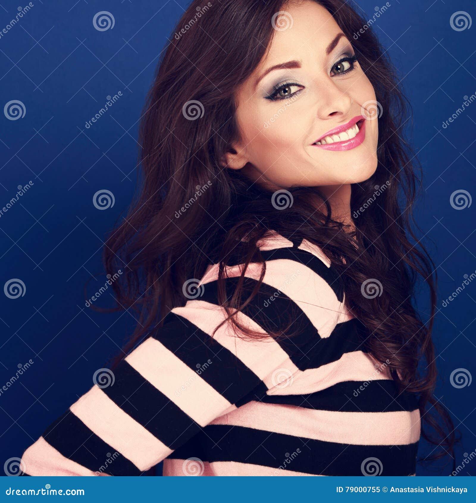 A mulher de sorriso bonita com vista longa encaracolado do penteado frien