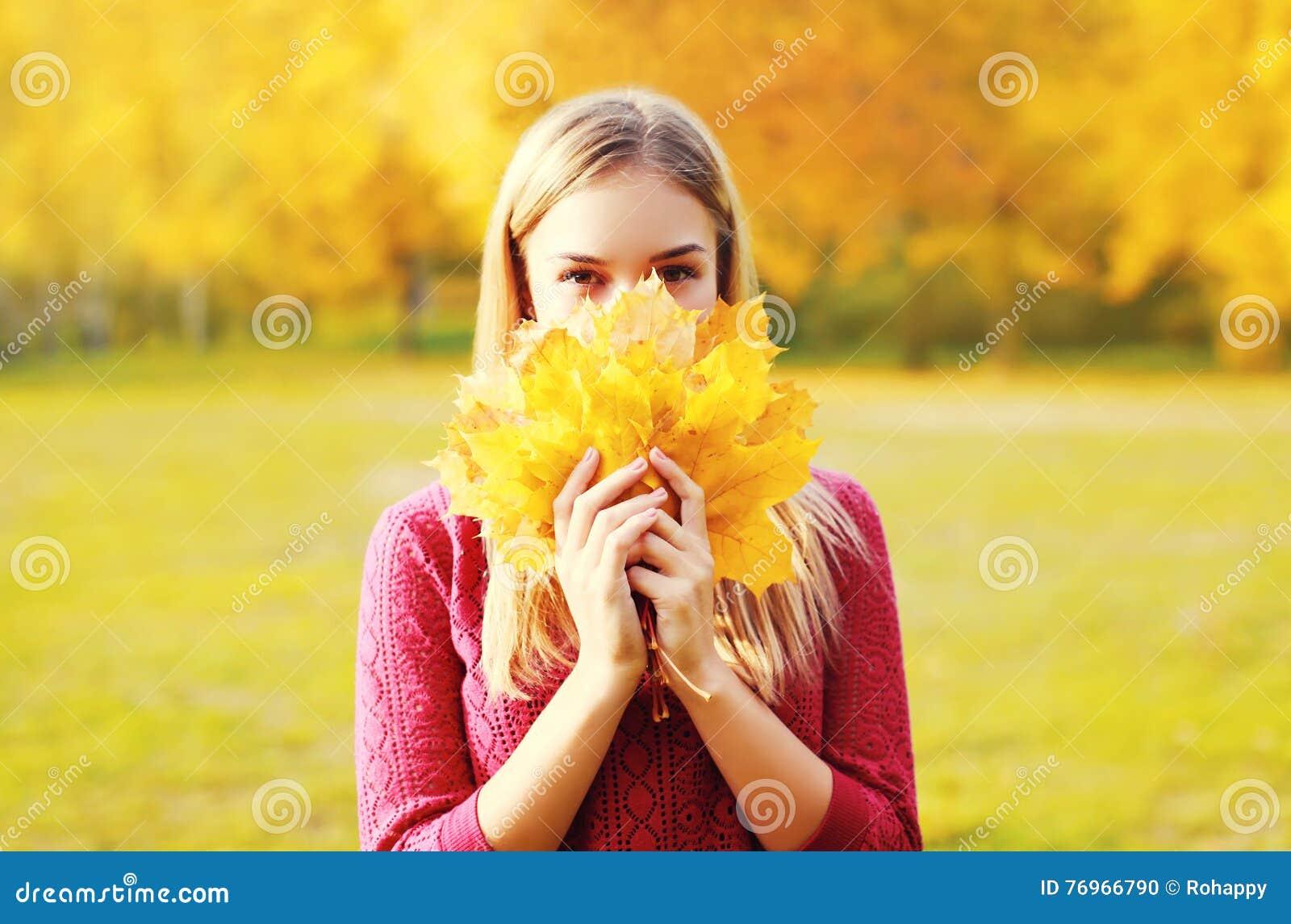 A mulher de sorriso bonita do retrato esconde suas folhas de bordo do amarelo da cara no outono ensolarado