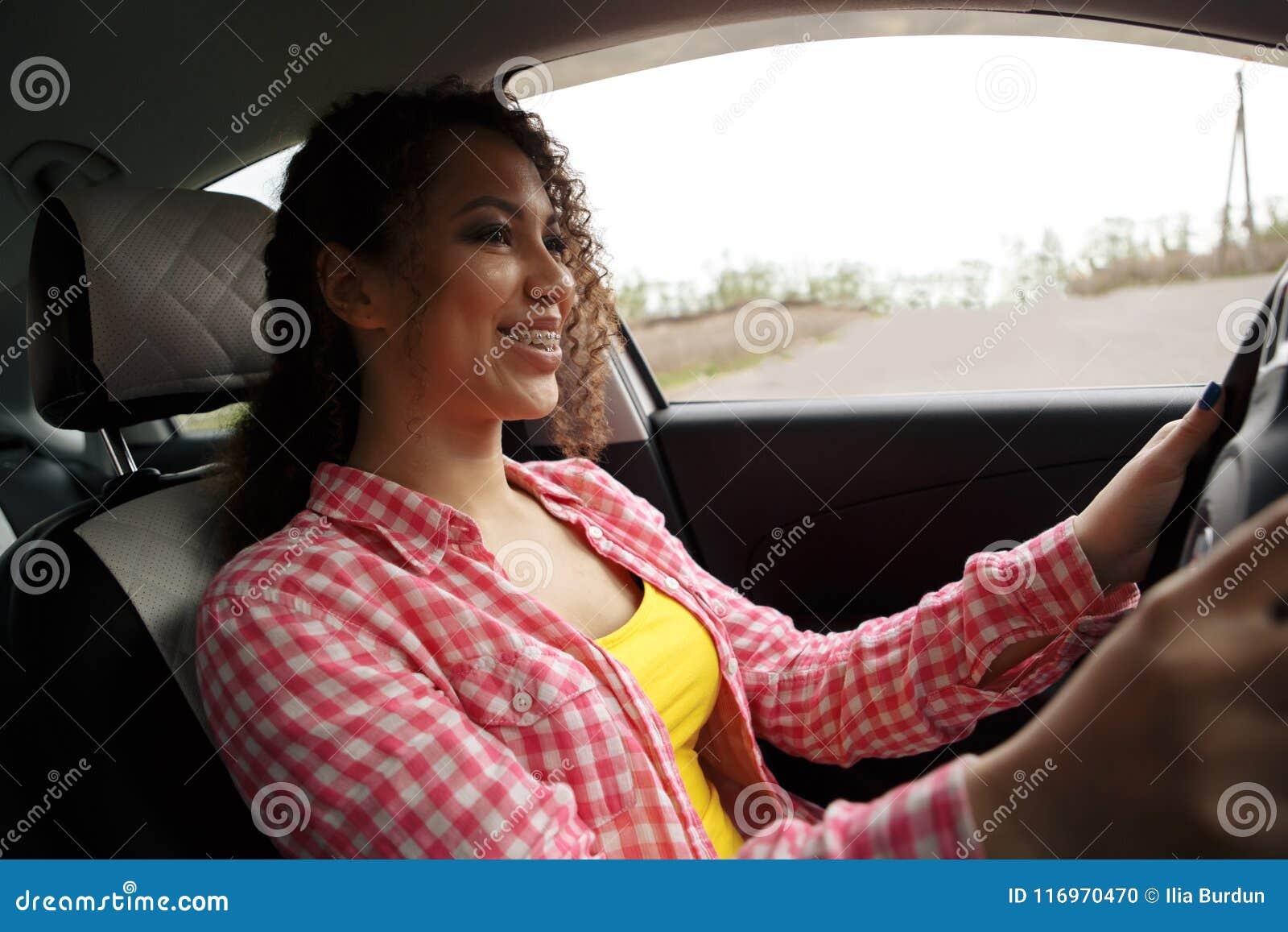 Mulher de sorriso bonita nova que conduz um carro Sua filha bonito que senta-se na parte traseira e que aprecia