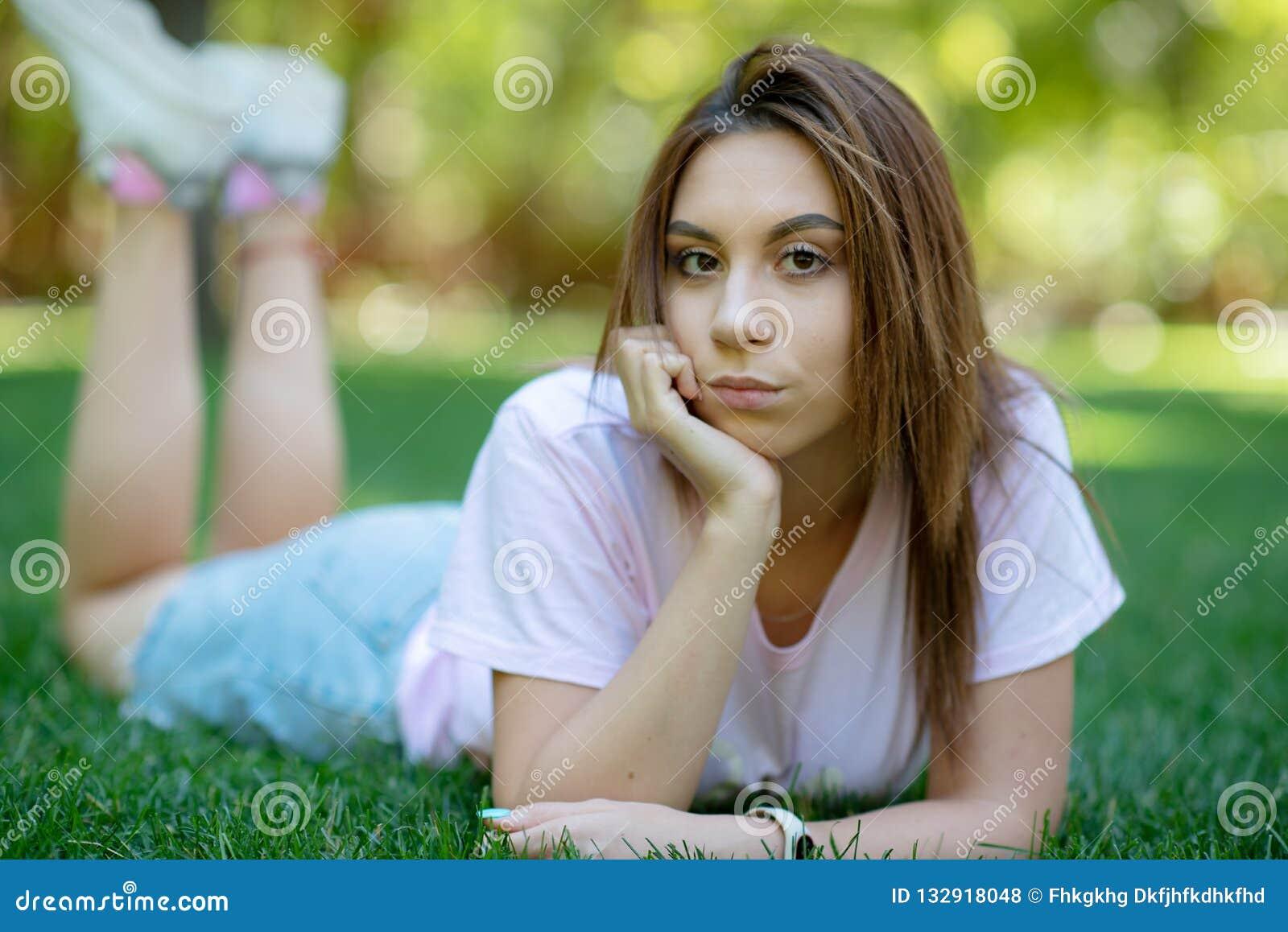 Mulher de sorriso bonita que encontra-se em uma grama exterior