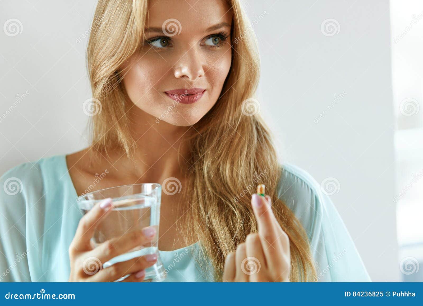 Mulher de sorriso bonita que toma o comprimido da vitamina Suplemento dietético