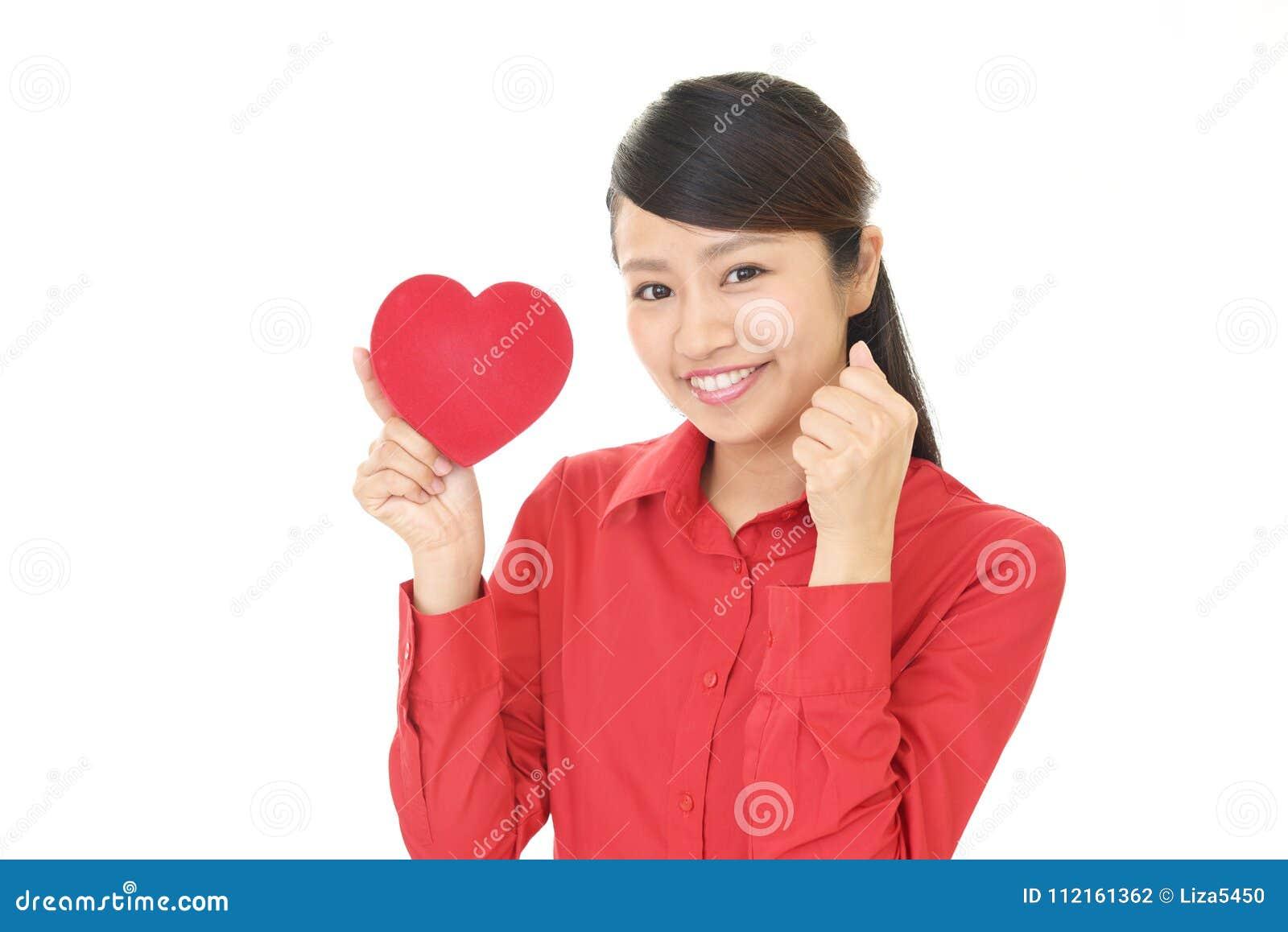 Mulher de sorriso com um coração vermelho