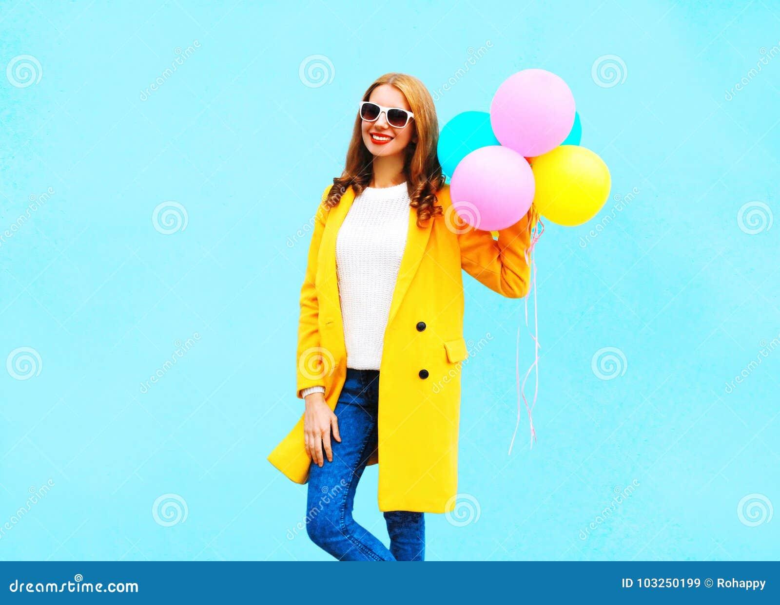 A mulher de sorriso da forma guarda balões de ar no revestimento amarelo