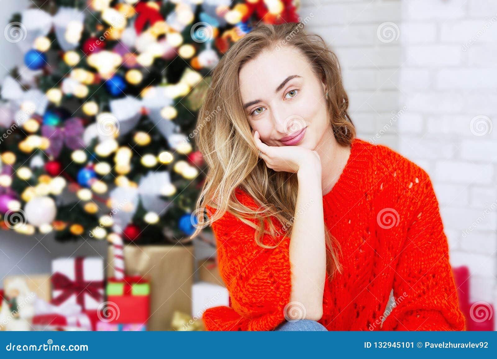 Mulher de sorriso do retrato no fundo interior do Natal Conceito do ano novo Foco seletivo Árvore e festões de Natal