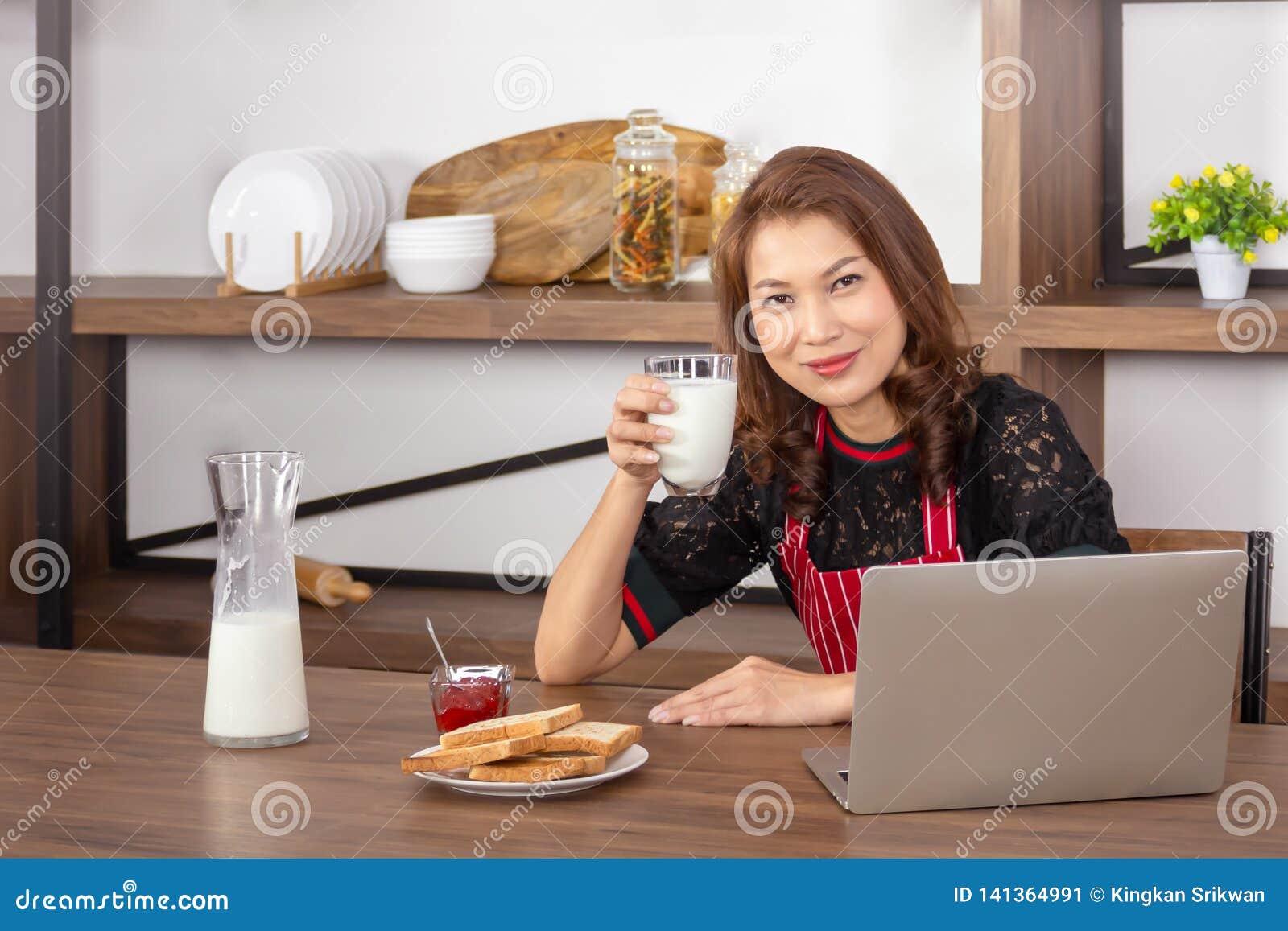 Mulher de sorriso e guardar um vidro do leite