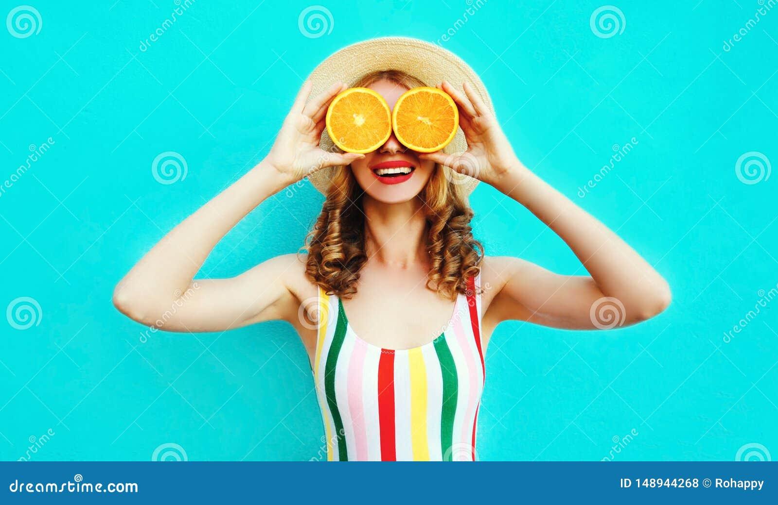 Mulher de sorriso feliz do retrato do ver?o que realiza em suas m?os duas fatias de fruto alaranjado que escondem seus olhos no c
