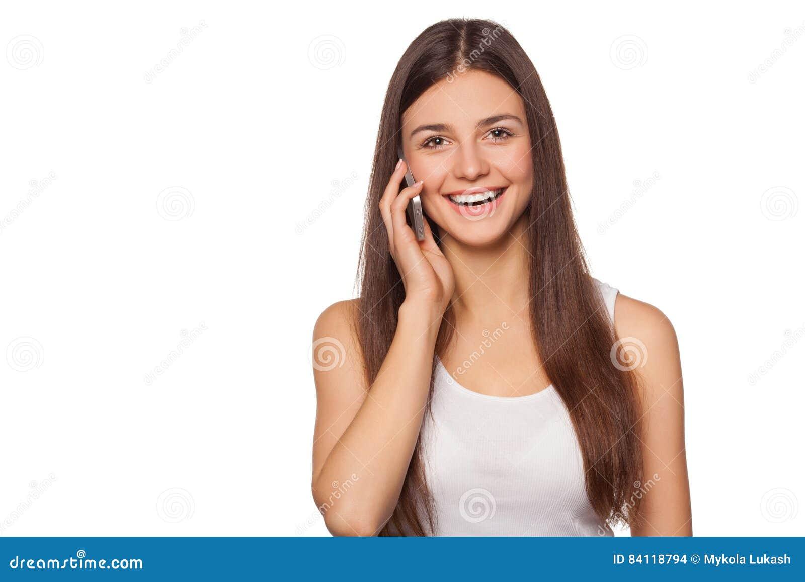 Mulher de sorriso feliz que fala no telefone celular, isolado no fundo branco Menina bonita com um smartphone