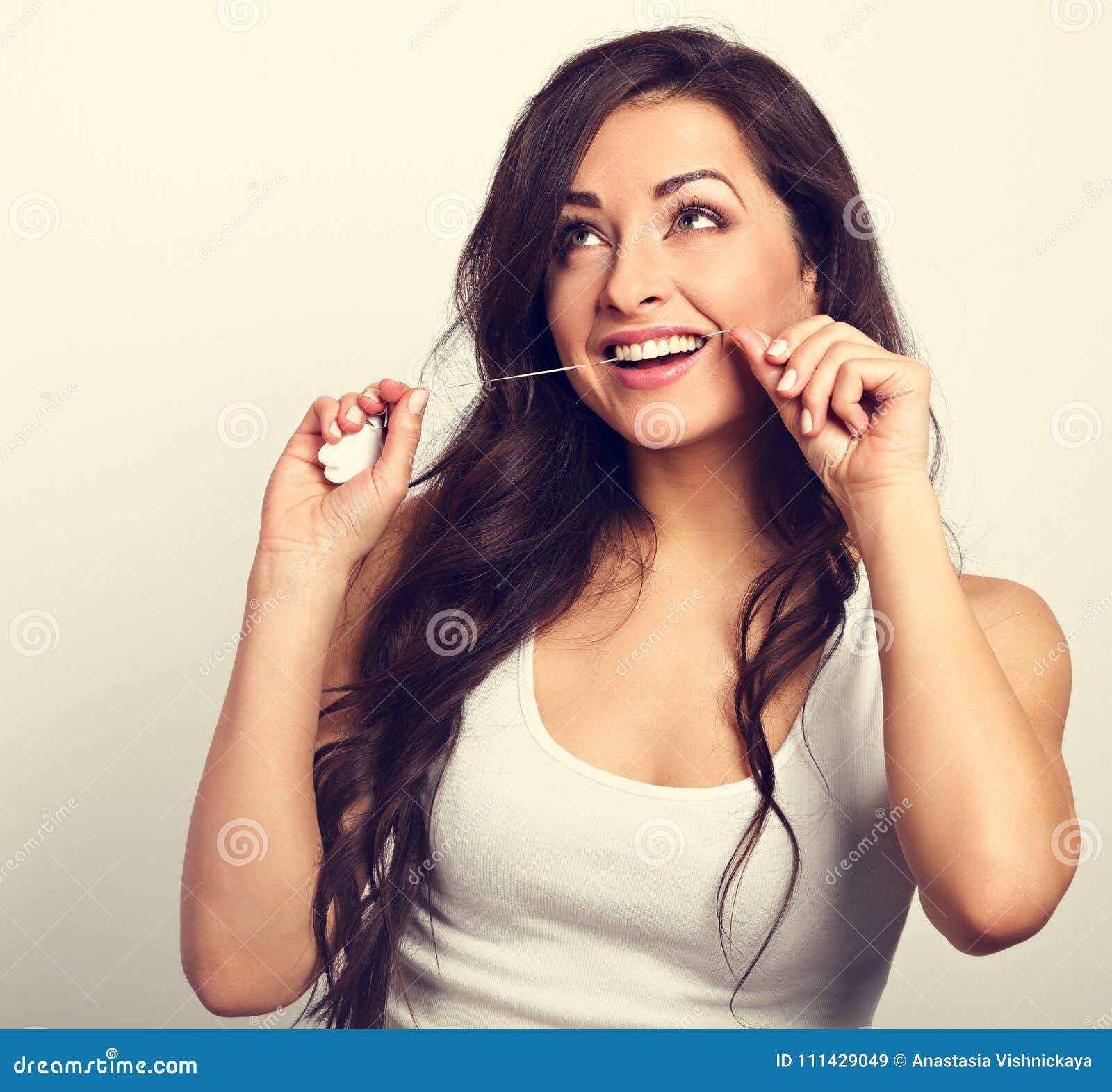 b9f5daf52 Mulher de sorriso feliz que limpa os dentes o fio dental Higiene dental  Retrato tonificado do vintage. Mais imagens de stock similares