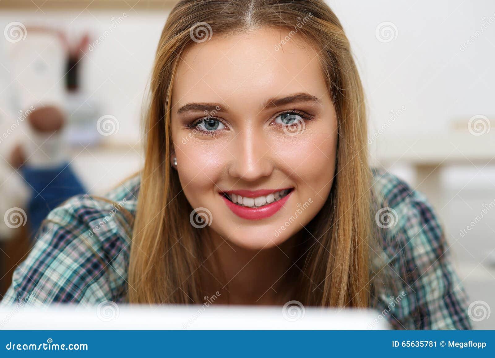 Mulher de sorriso loura bonita que encontra-se no assoalho com comput do portátil