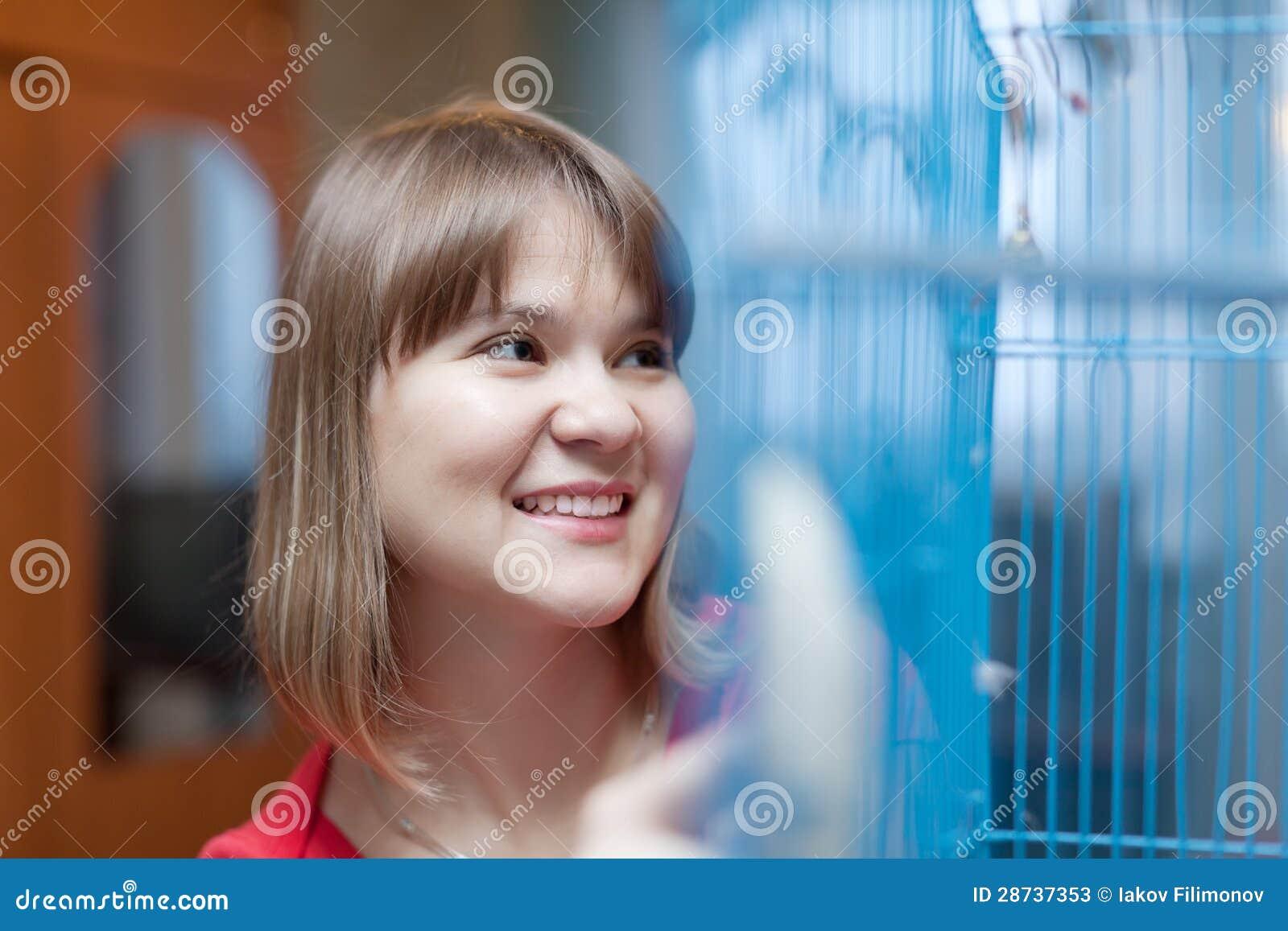 Mulher de sorriso na gaiola com animais de estimação