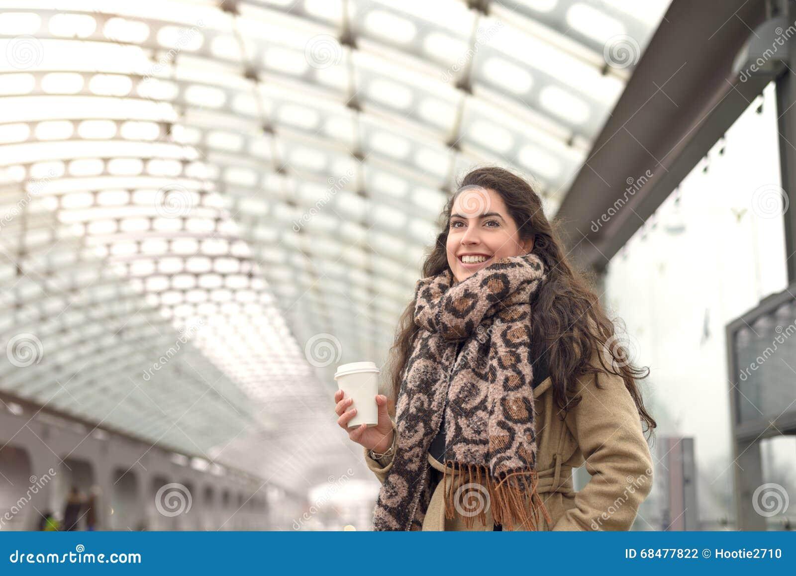 Mulher de sorriso no revestimento com café na estação
