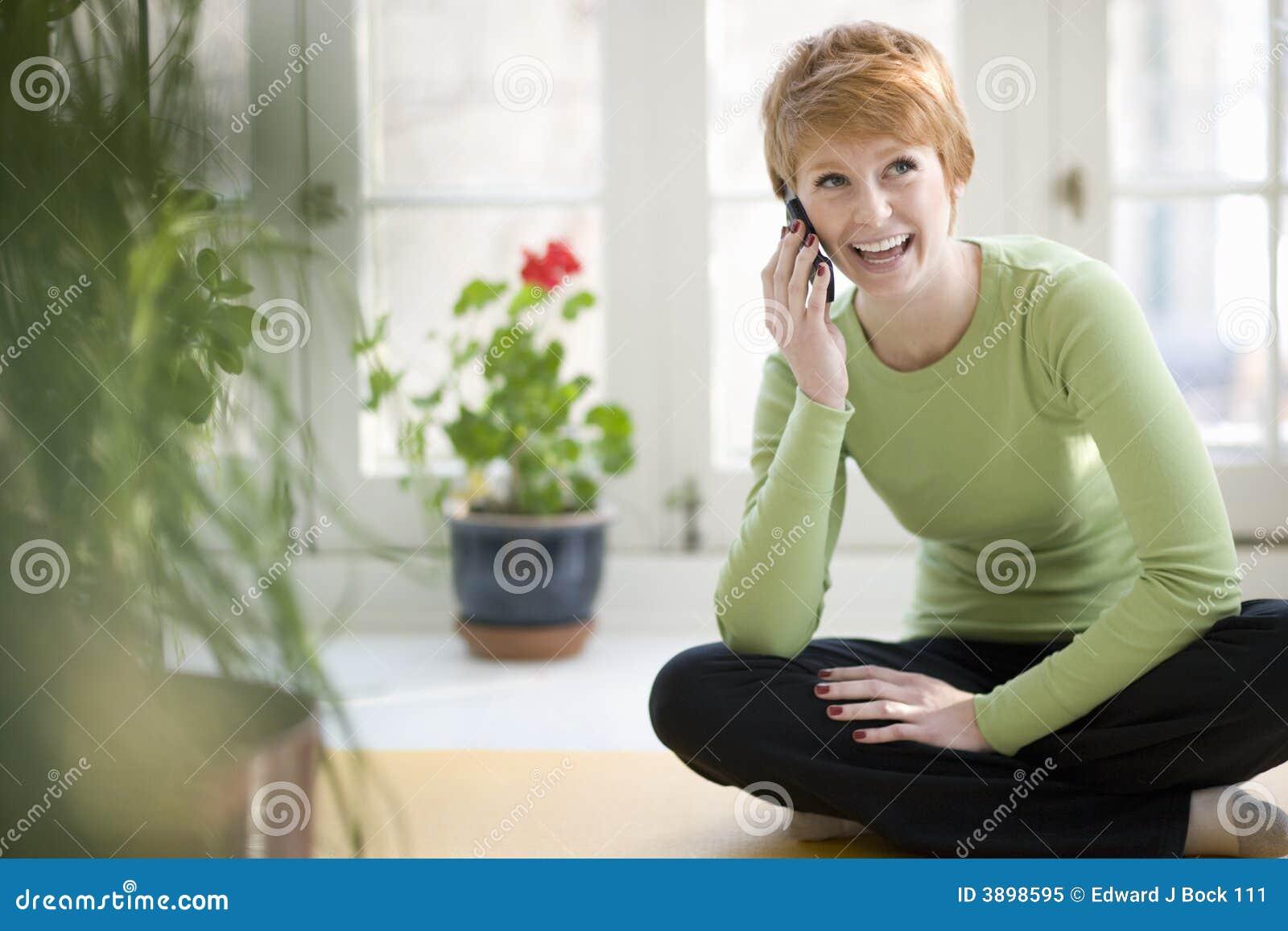 Mulher de sorriso no telefone de pilha