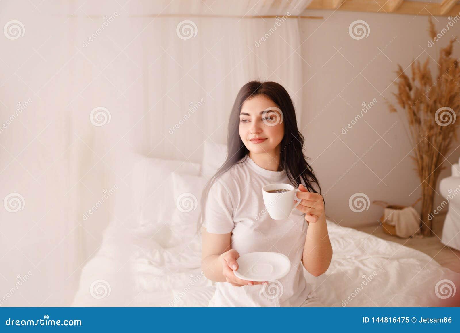 A mulher de sorriso nova aprecia o caf? da manh? na cama
