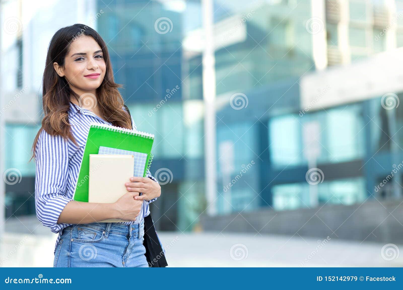 Mulher de sorriso nova que guarda livros, estudo, educação, conhecimento, conceito do objetivo