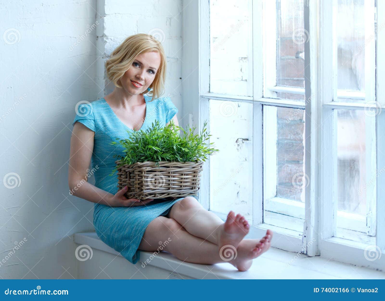 Mulher de sorriso nova que senta-se na soleira com a caixa com plantas
