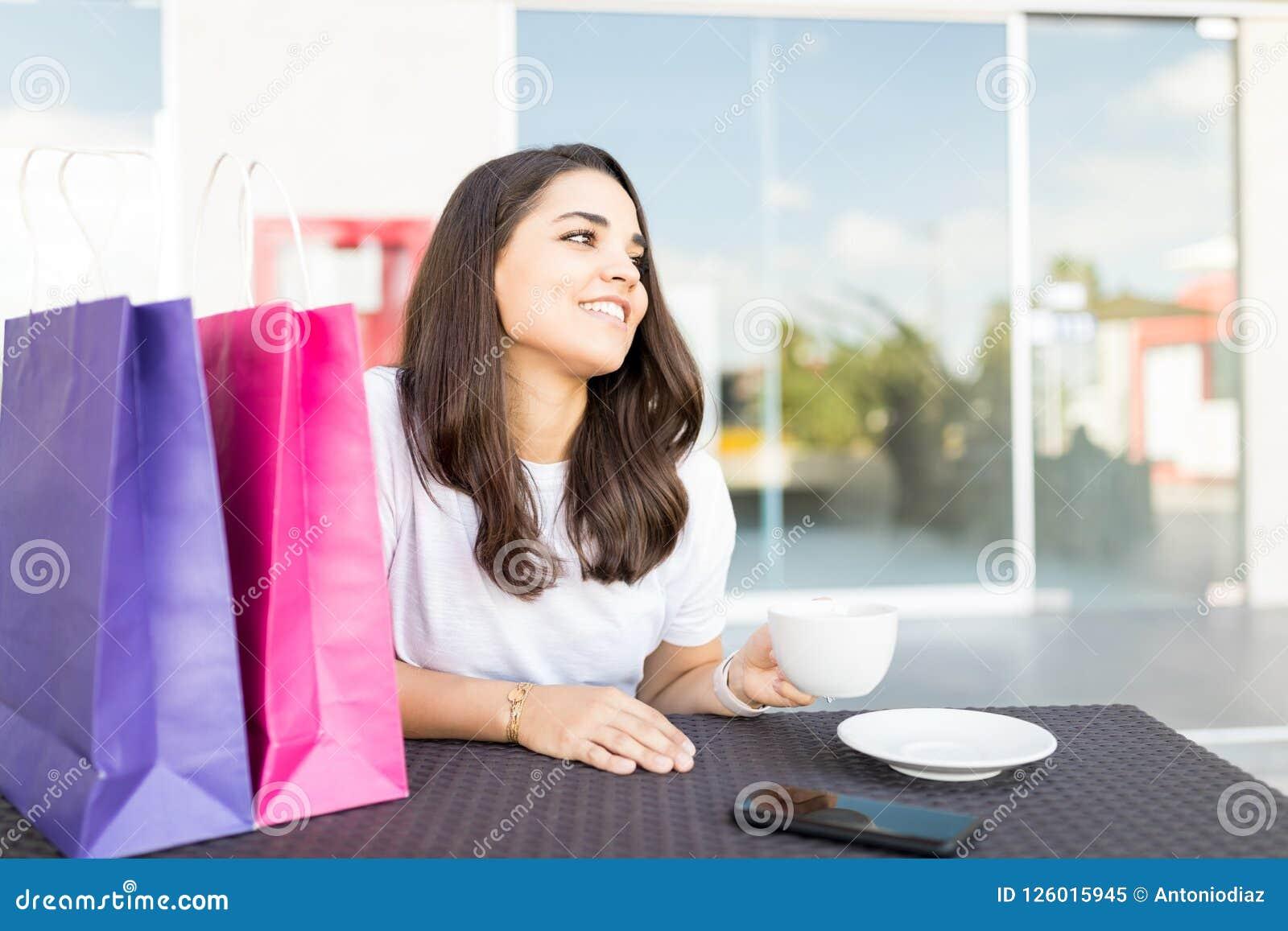 Mulher de sorriso que come o café após a compra no café na alameda