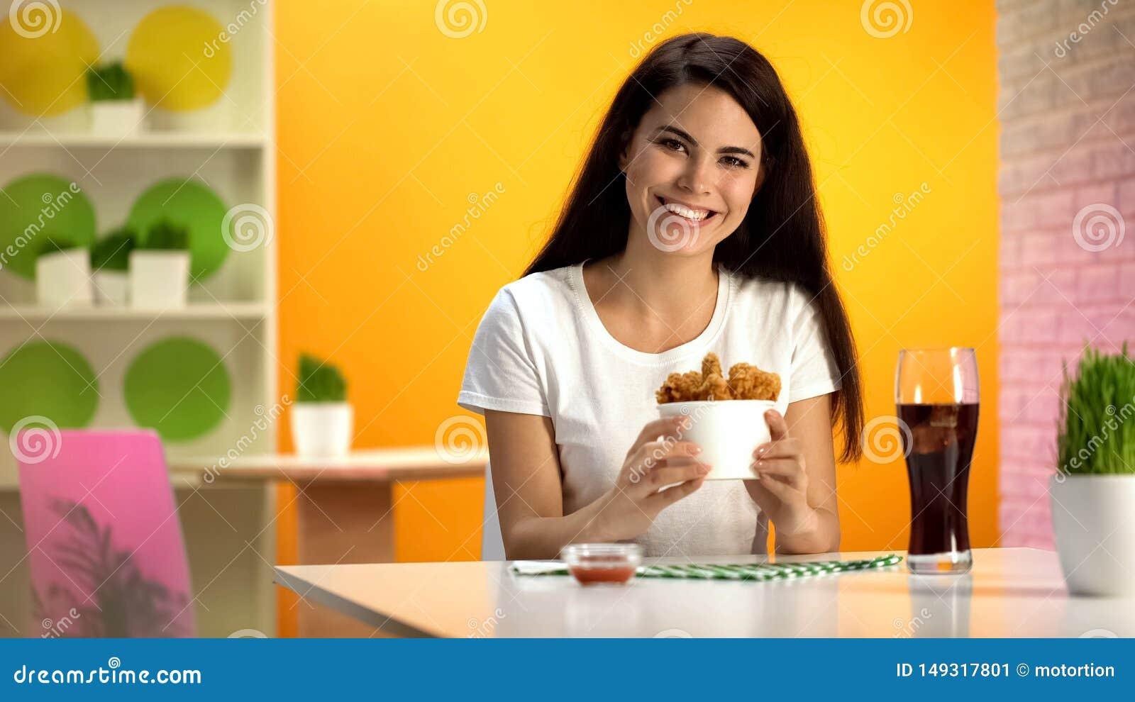 Mulher de sorriso que guarda a bacia descart?vel com o frango frito fri?vel, apreciando a refei??o