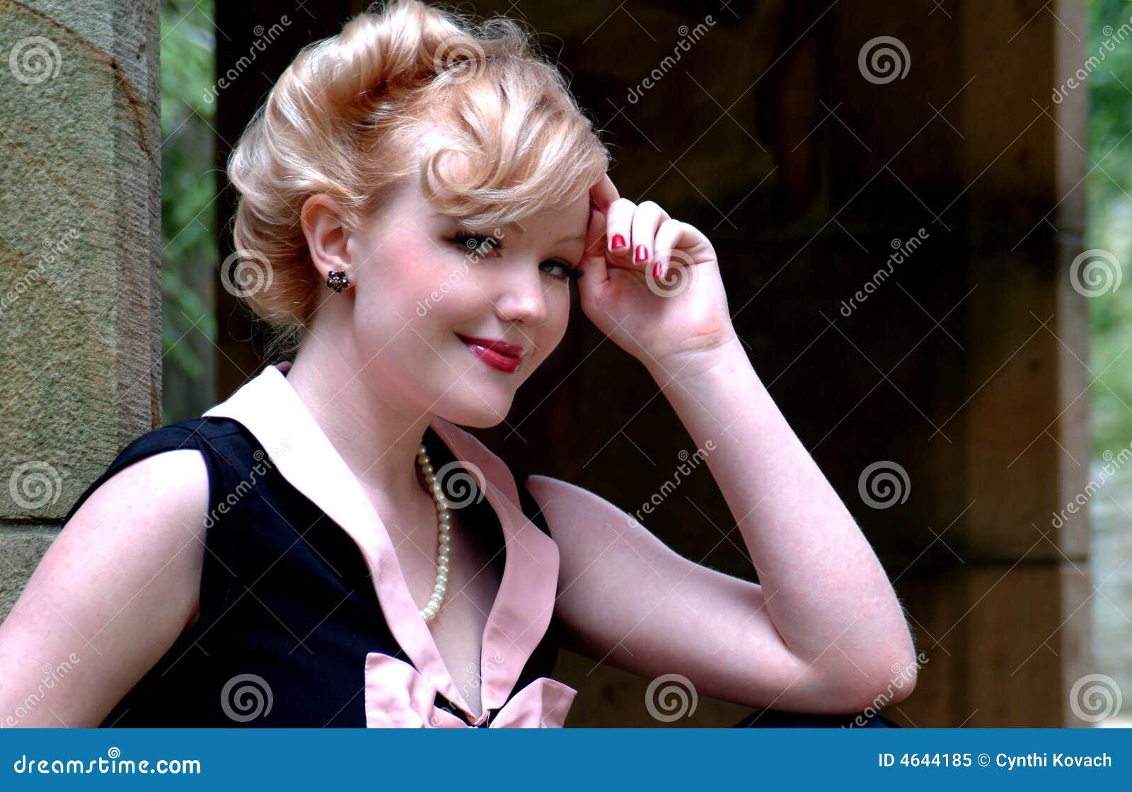 Mulher de sorriso que inclina-se na mão