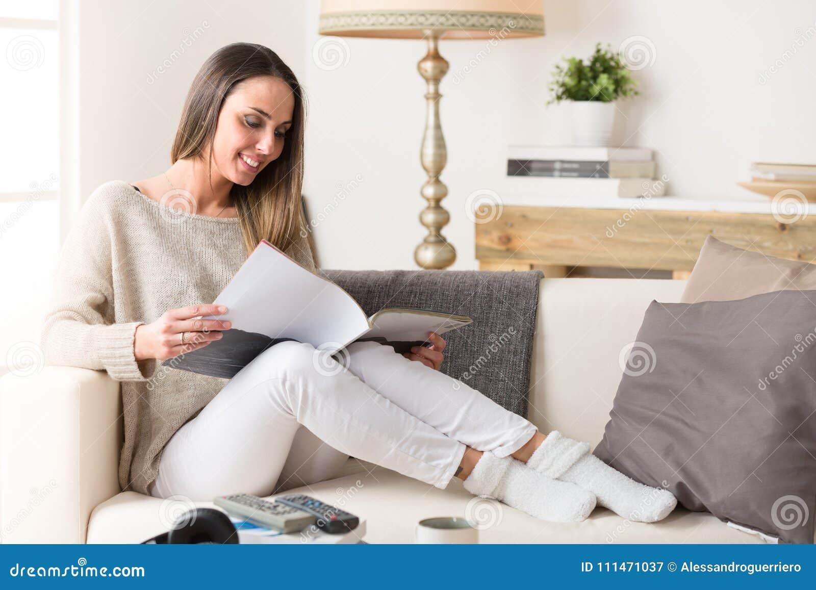 Mulher de sorriso que lê um compartimento em um sofá
