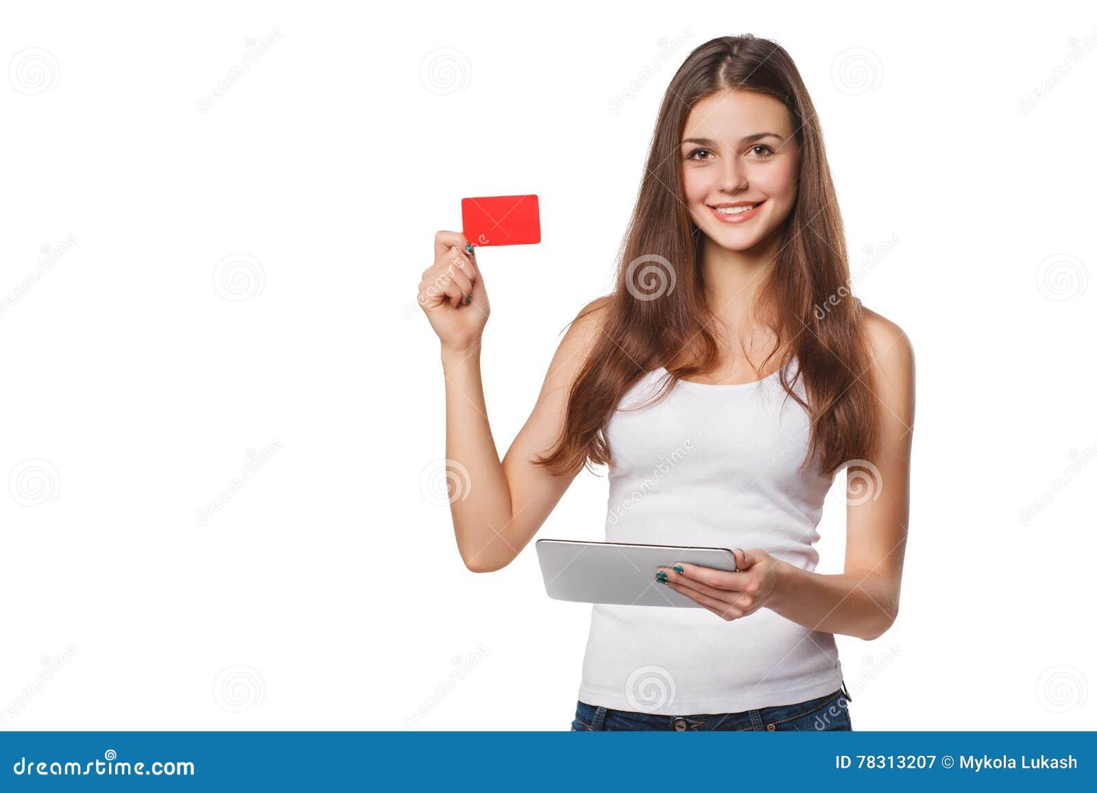 A mulher de sorriso que mostra o cartão de crédito vazio mantém o PC da tabuleta disponivel, no t-shirt branco, isolado sobre o f