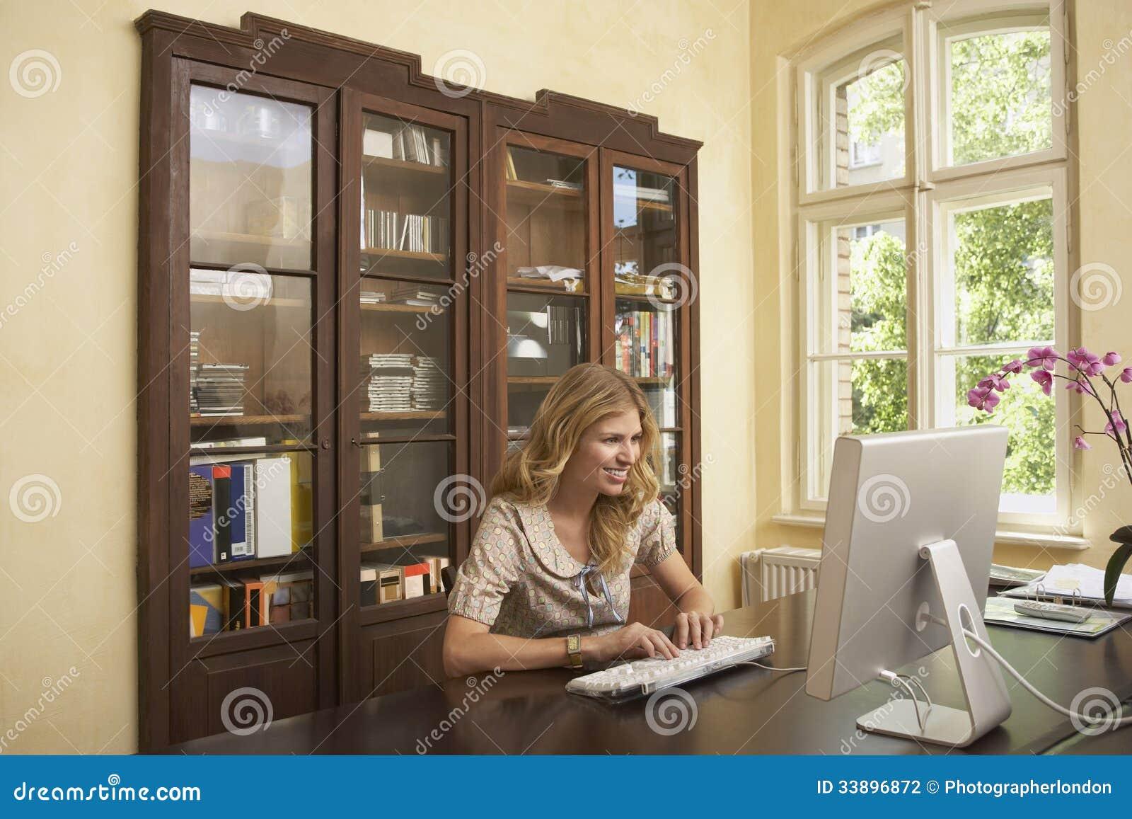 Mulher de sorriso que usa o computador na sala de estudo