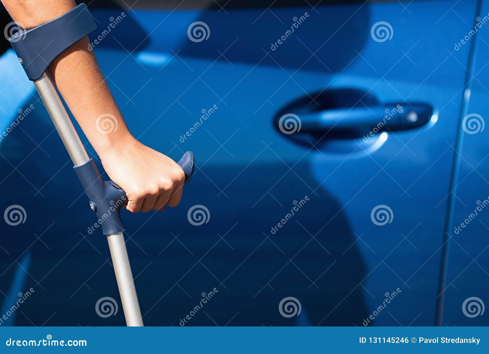 Mulher deficiente com a porta de abertura das muletas de um carro