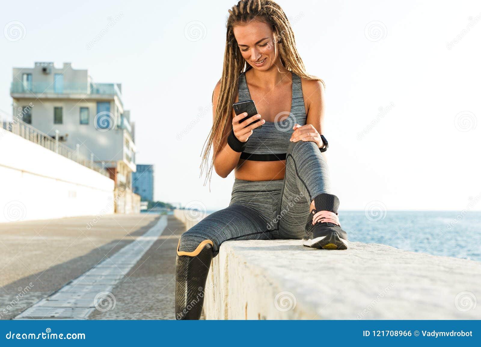 Mulher deficiente de sorriso do atleta com pé protético