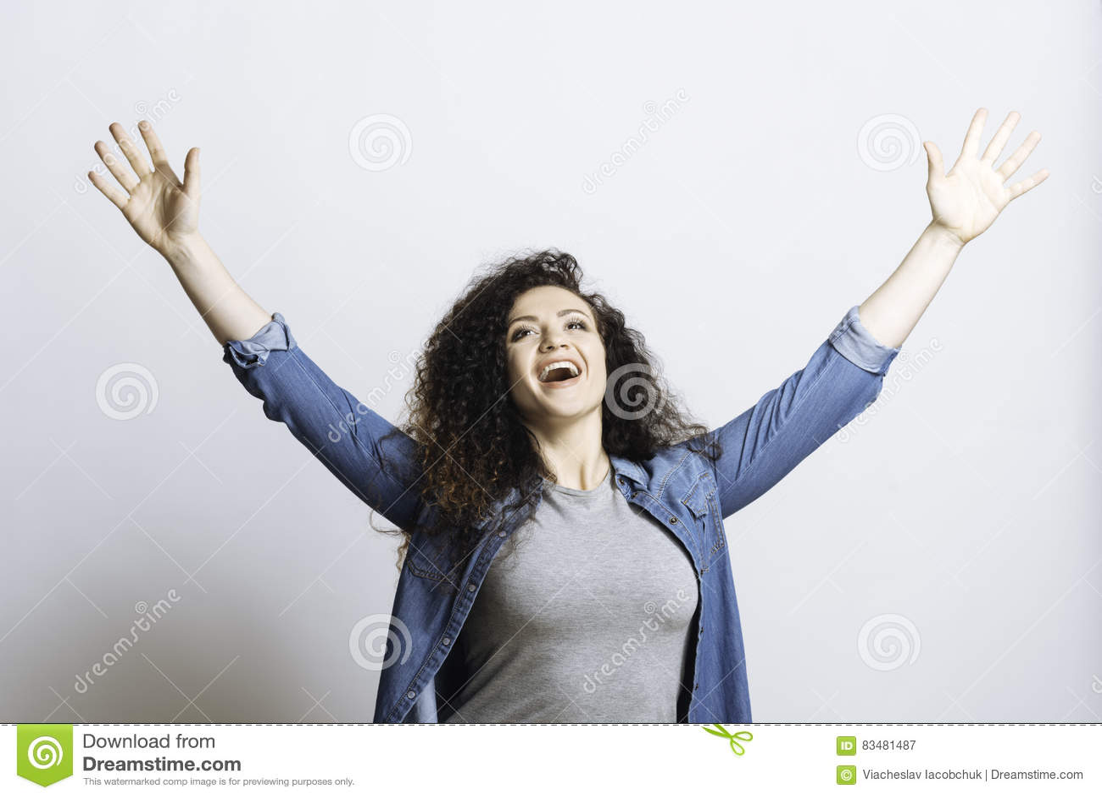 Mulher deleitada positiva que levanta as mãos